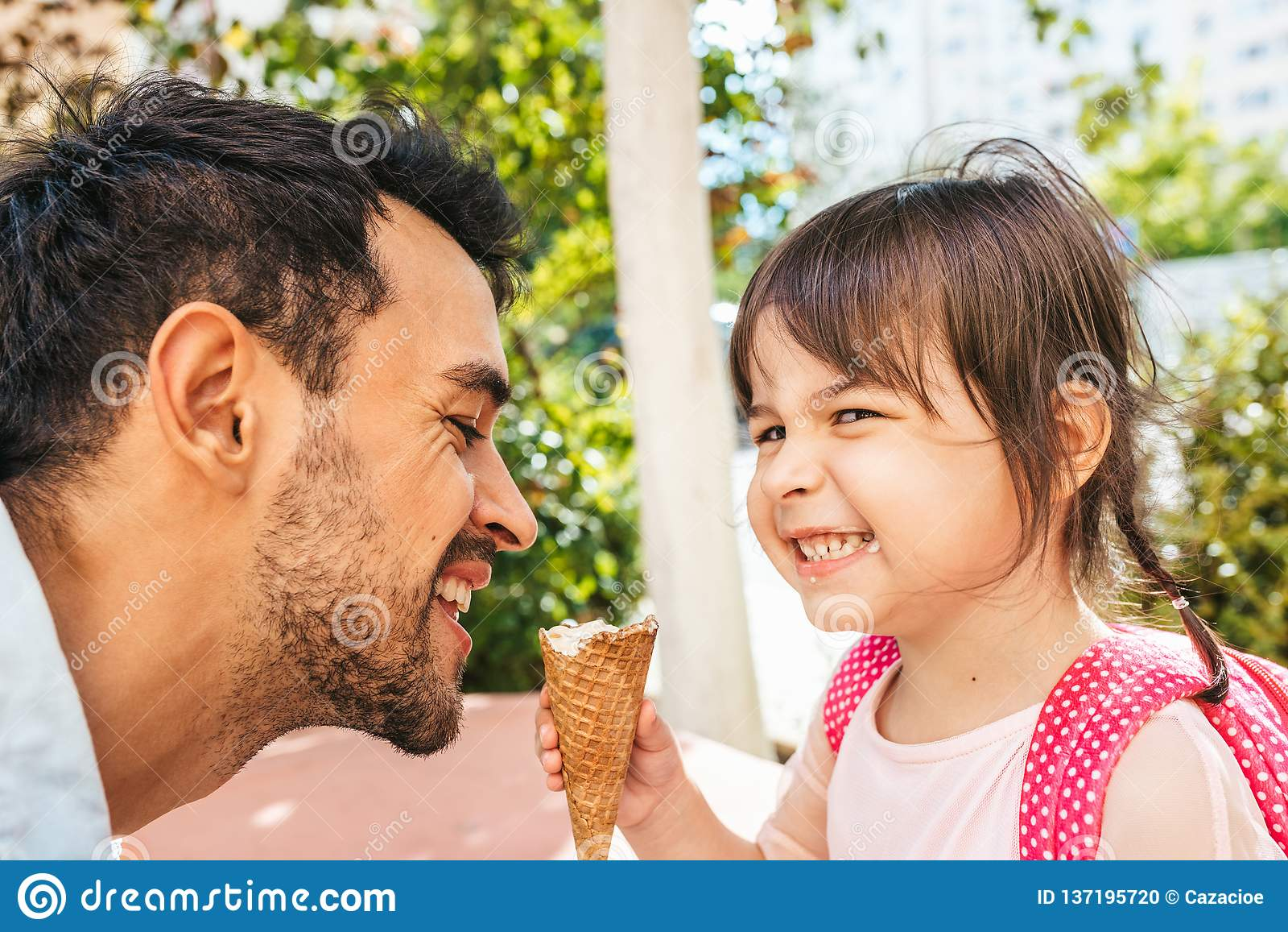 Opinião lateral do close up a menina bonito feliz que senta-se com o paizinho considerável que come o gelado fora Criança da meni