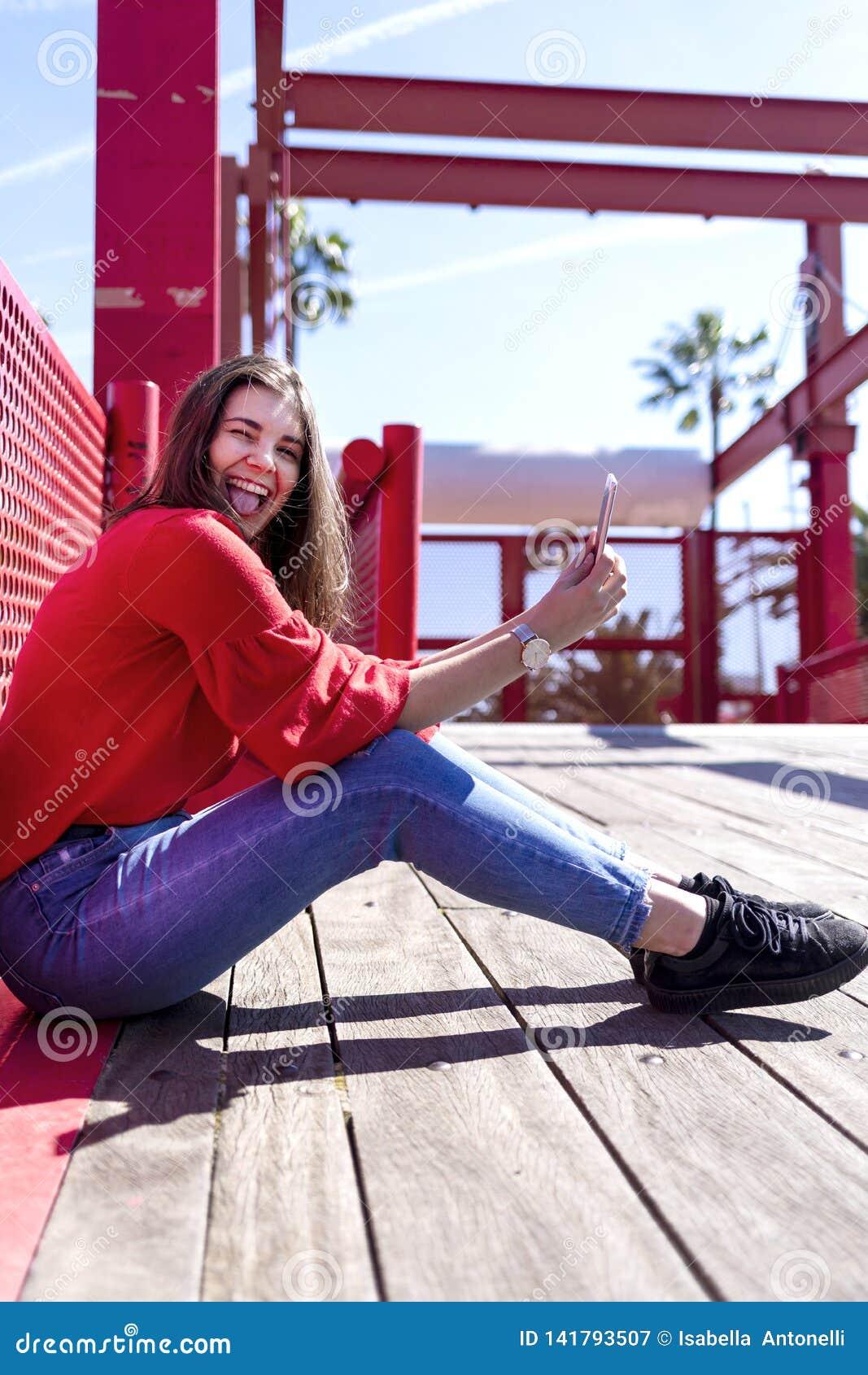 Opinião lateral a jovem mulher bonita feliz que veste a roupa urbana que senta-se na terra e que olha a câmera ao usar um telefon