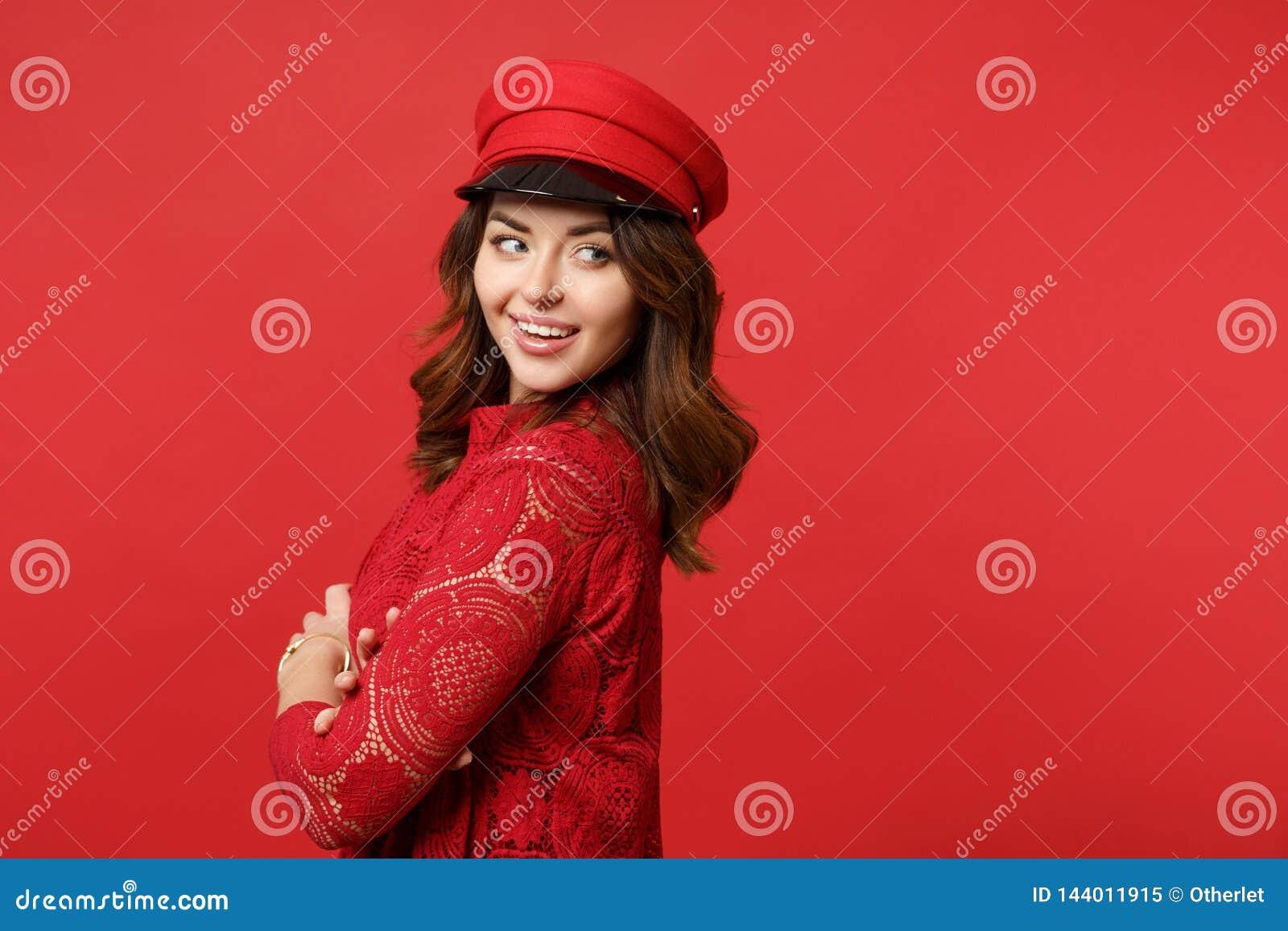 A opinião lateral a jovem mulher de sorriso no vestido do laço, mão da terra arrendada do tampão cruzou a vista isolada de lado n