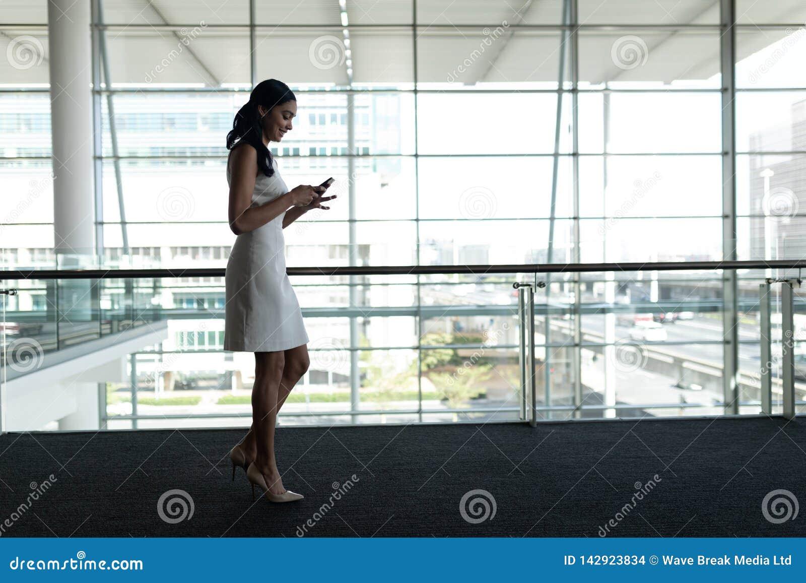 Opinião lateral a mulher de negócios que usa o telefone celular no escritório e andando em uma passagem do tapete