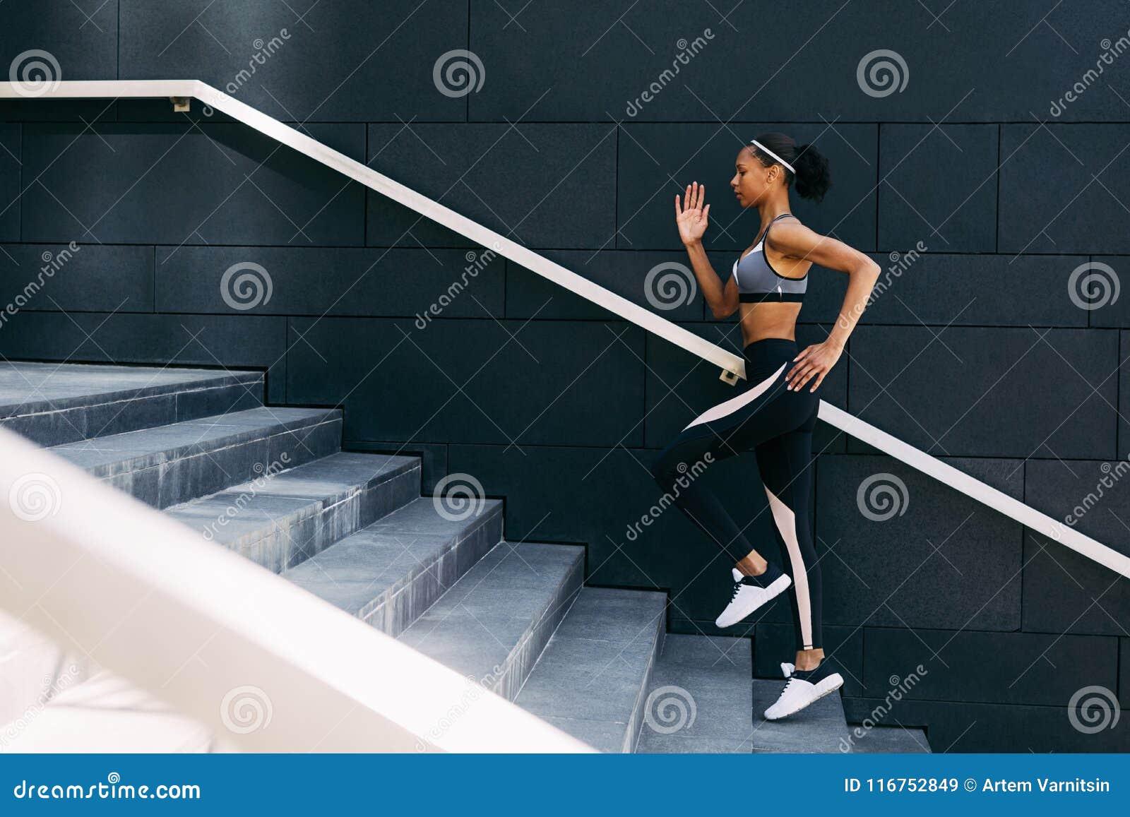 Opinião lateral a mulher no sportswear que corre acima as etapas na cidade