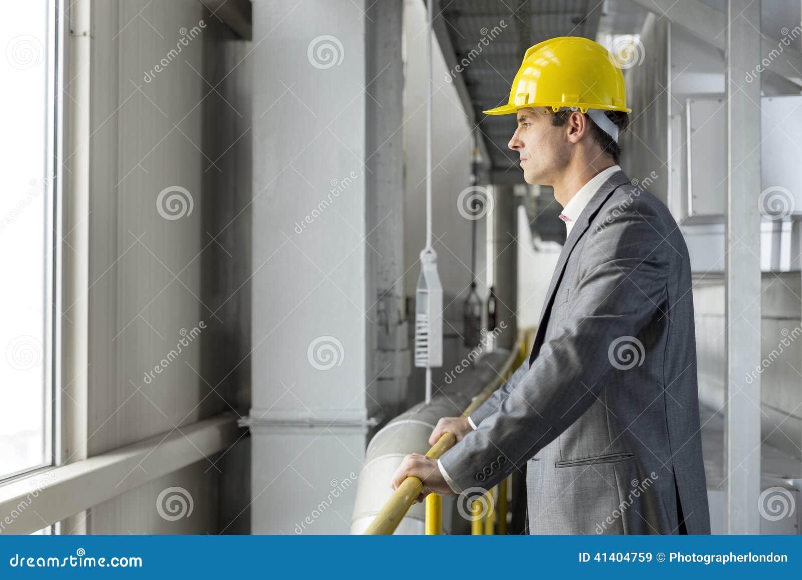Opinião lateral o arquiteto masculino pensativo que está cercando na indústria
