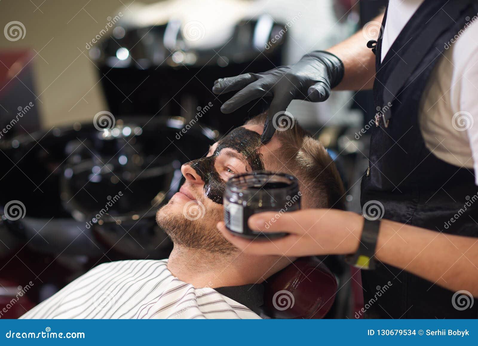 Opinião lateral o barbeiro que põe a máscara preta sobre a cara de masculino