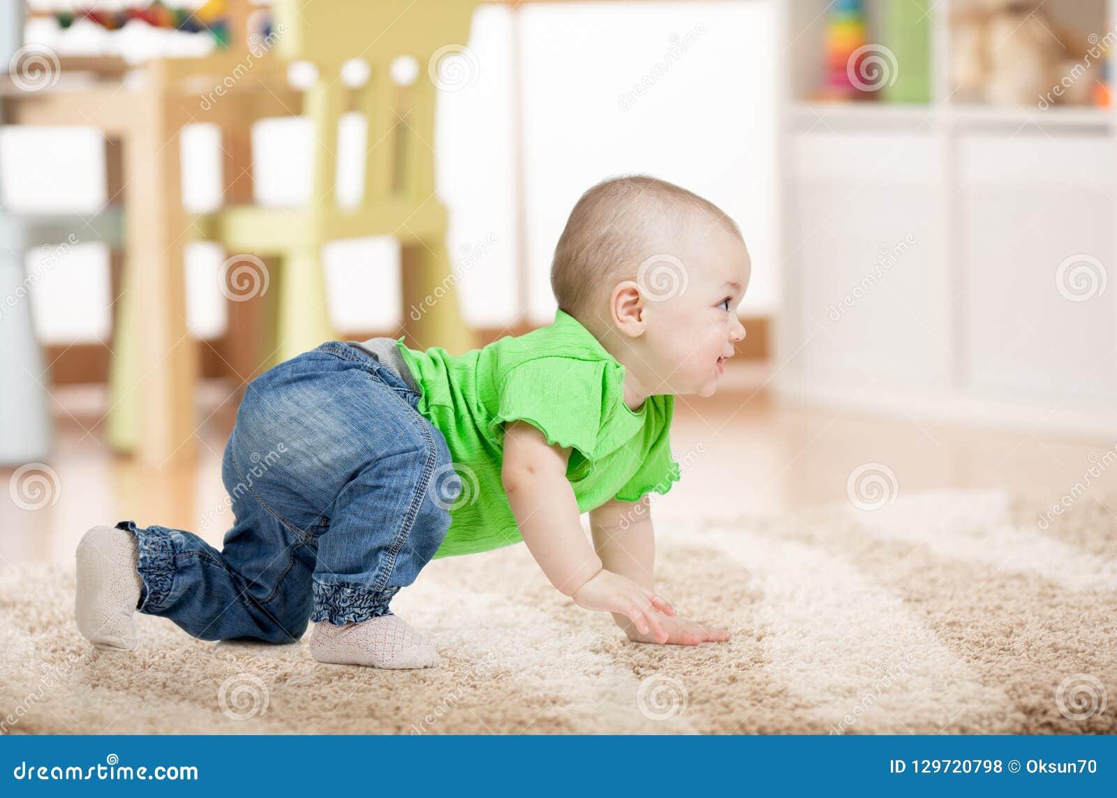 Opinião lateral o bebê que rasteja no tapete no assoalho na sala de crianças