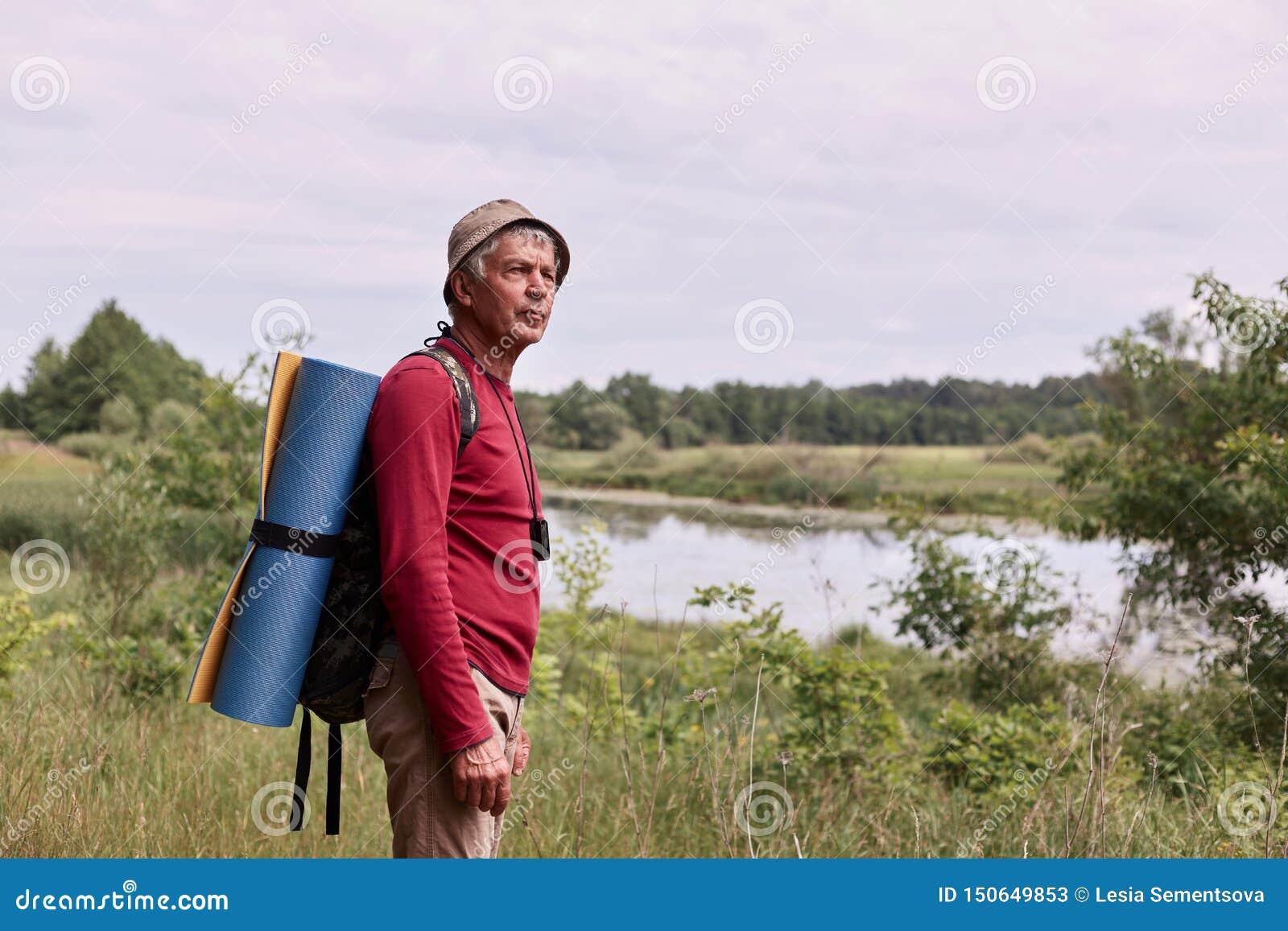 Opinião lateral o homem do eldery com trouxa e o tapete azul, apreciação de admirar a vista majestosa do rio ao andar em maravilh