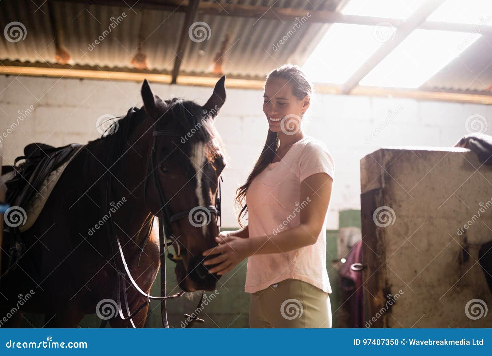 Opinião lateral o jóquei fêmea que afaga o cavalo