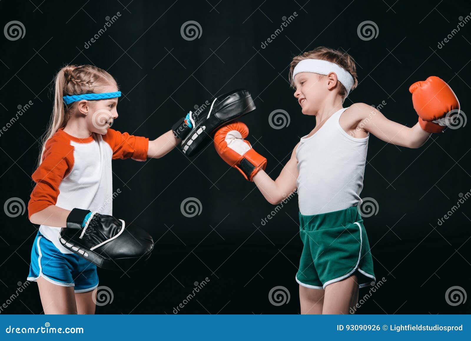 Opinião lateral o menino e a menina no encaixotamento do sportswear isolados no preto