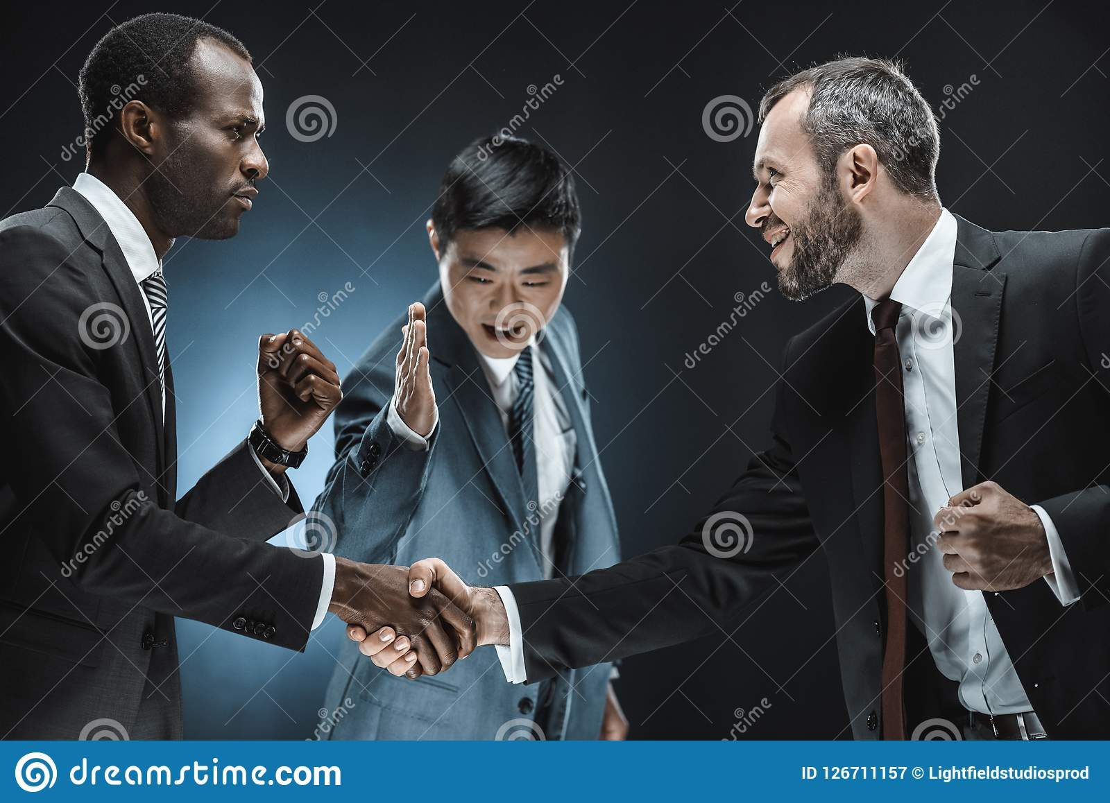 Opinião lateral os sócios comerciais multi-étnicos que agitam as mãos com o colega que está próximo perto