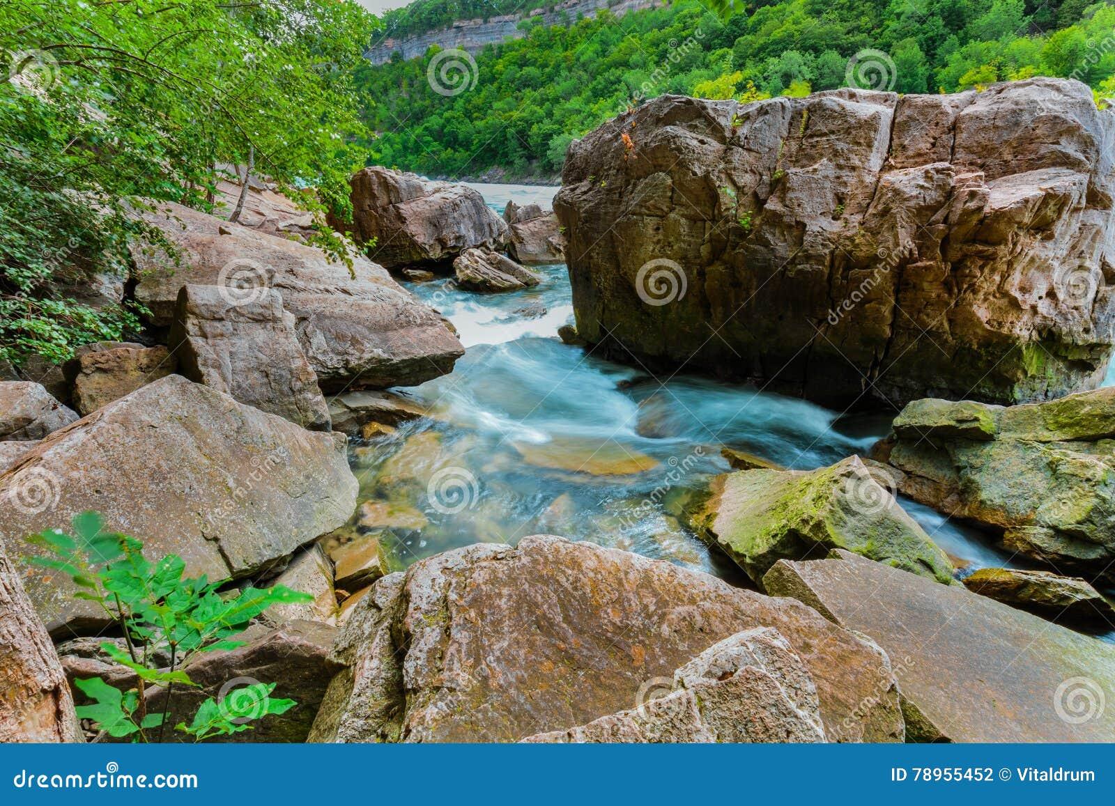 Opinião natural lindo da paisagem do rio de pressa da escarpa de Niagara Falls com rochas e fundo grandes das pedras