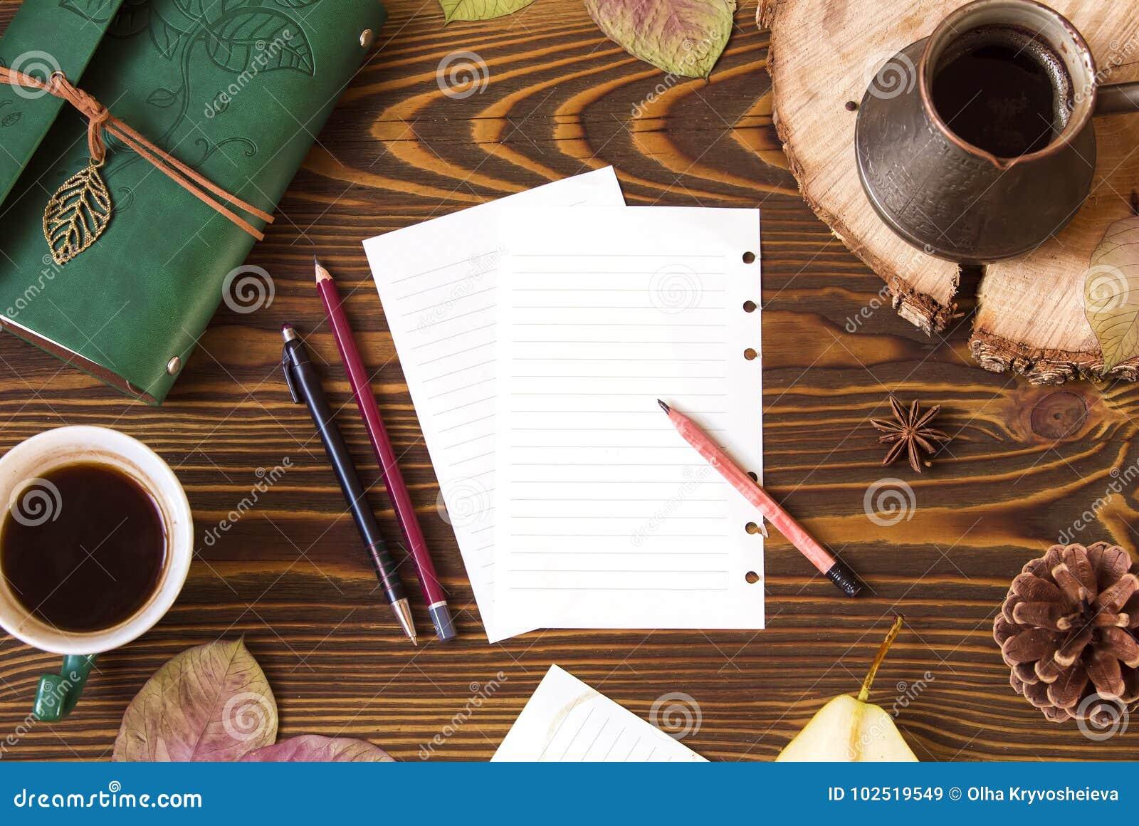 Opinião superior do local de trabalho Fundo de madeira com papel para notas, leiteria, cofee, ezve do  de Ñ, cone, folhas de out