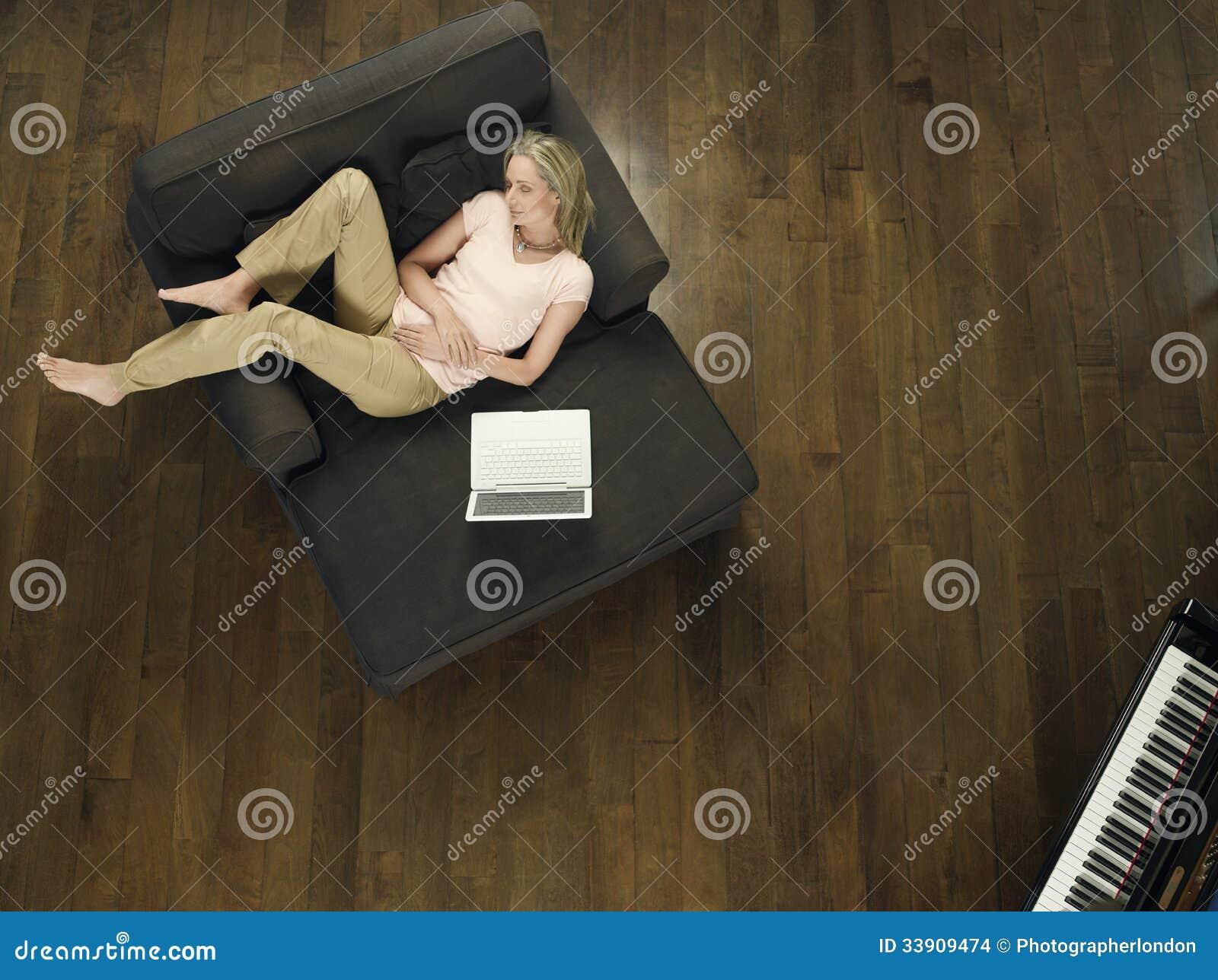 Opinião superior a mulher com portátil que dorme no sofá