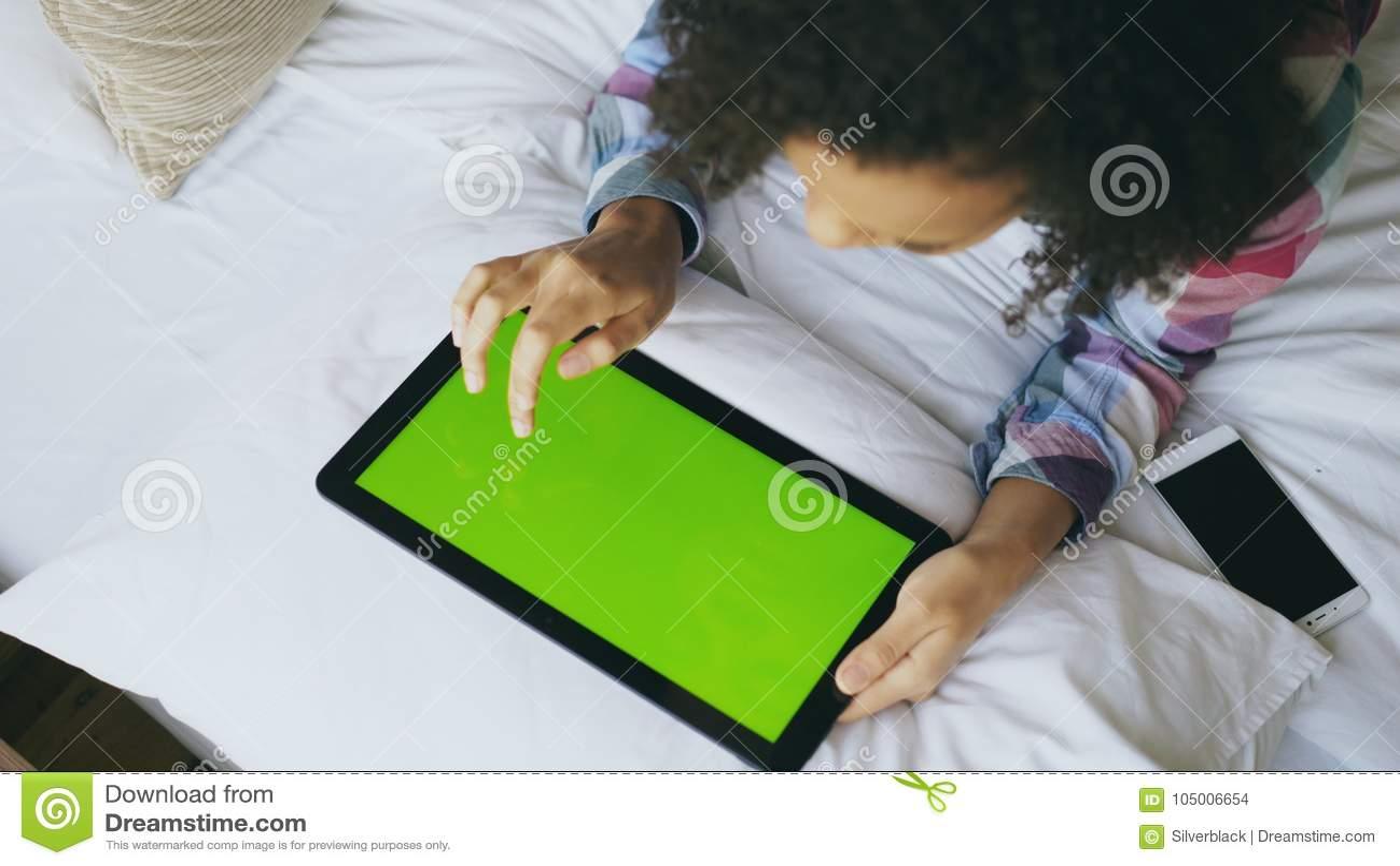 Opinião superior a mulher encaracolado da raça misturada que encontra-se na cama em casa que usa a tabuleta eletrônica com tela v