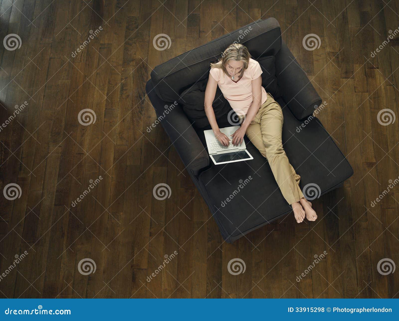 Opinião superior a mulher que usa o portátil no sofá