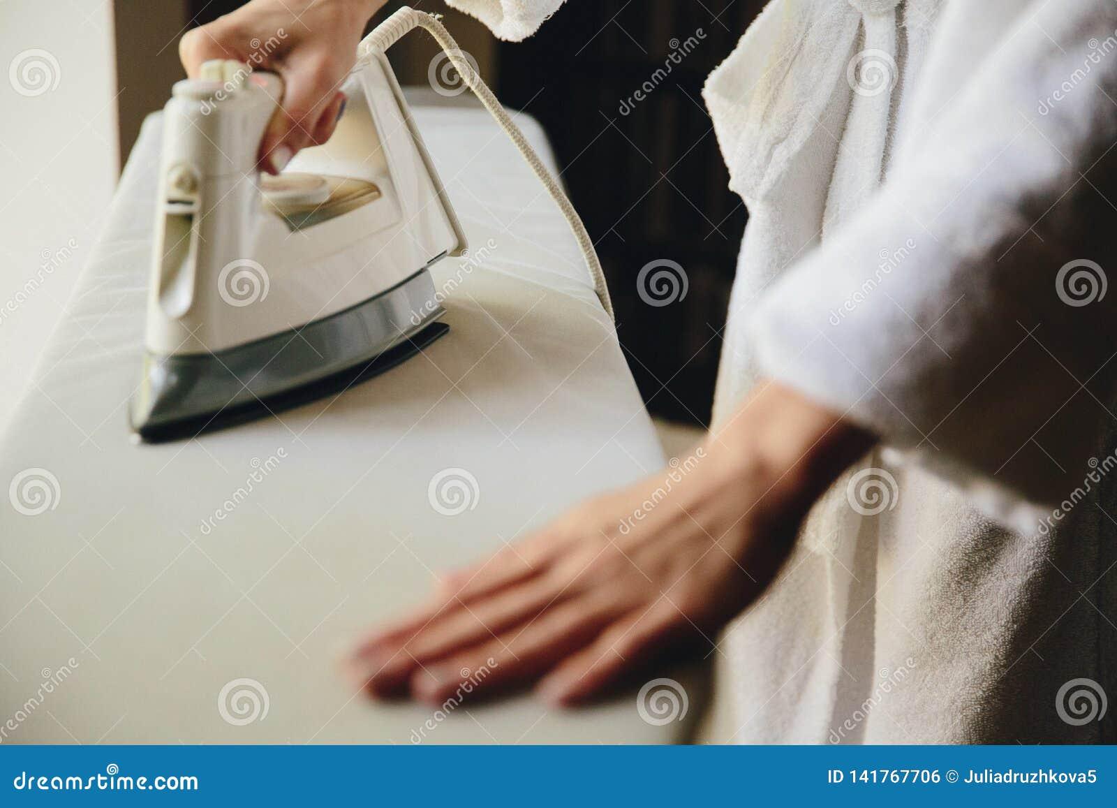 Opinião superior passando da roupa da mão fêmea isolada no fundo branco Jovem mulher com a camisa do homem passando do ferro vist