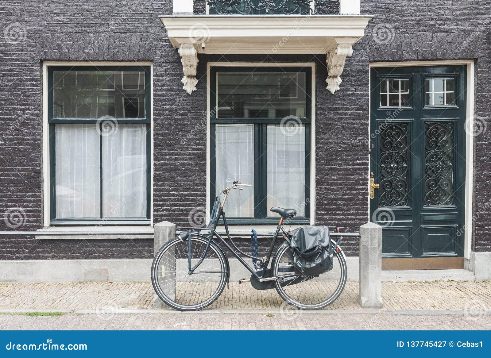 Opinião típica da rua de Amsterdão em Países Baixos com portas e as janelas e a bicicleta velhas do vintage