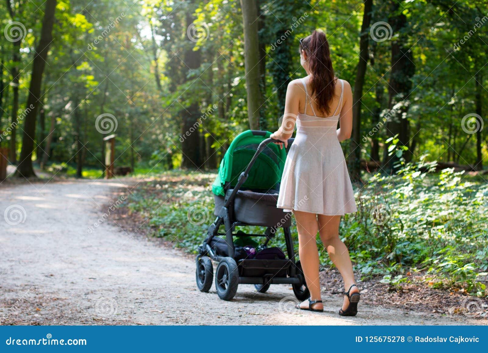A opinião traseira as mulheres atrativas que andam com o carrinho de criança na passagem a mais forrest natural, mãe nova está fo