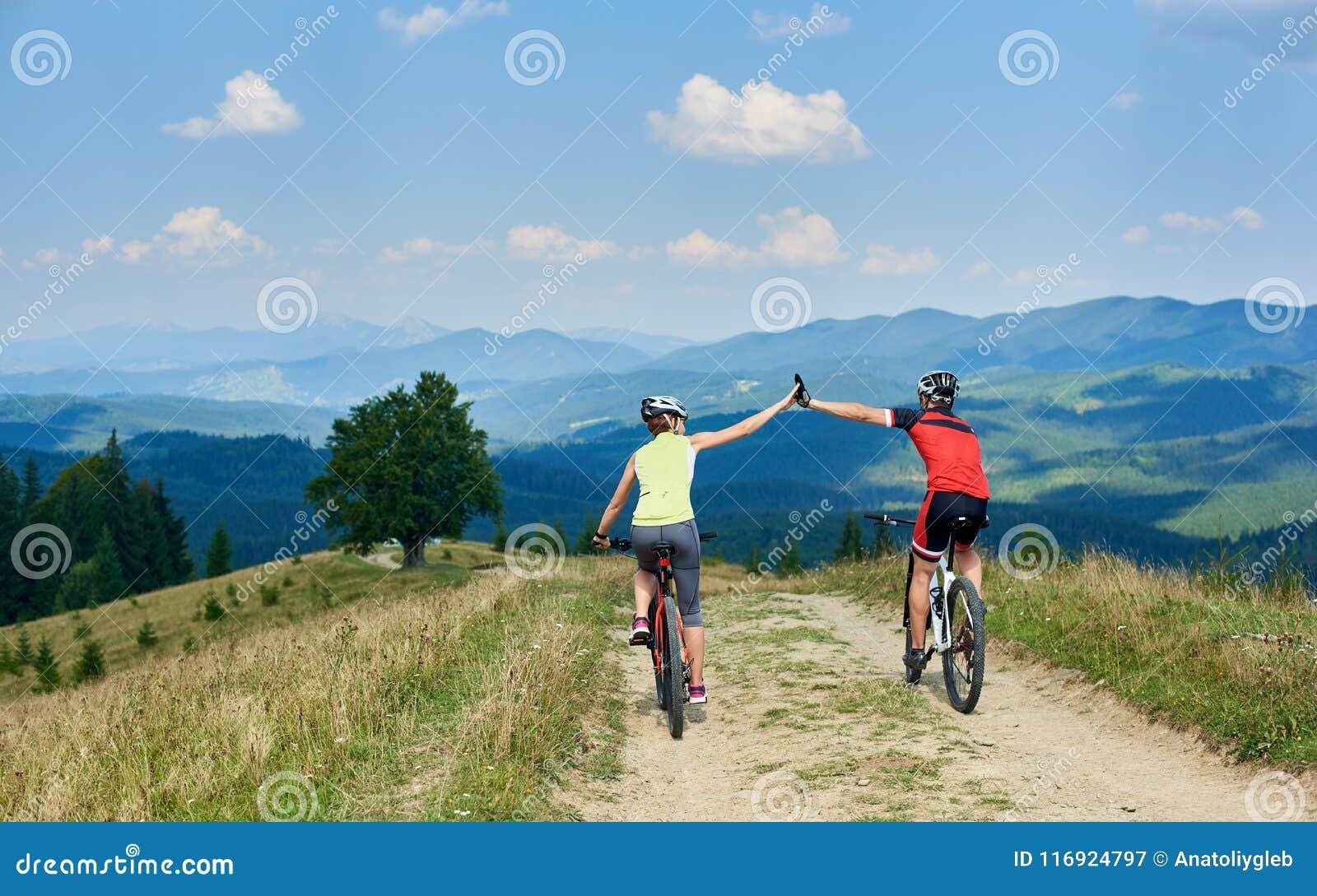 A opinião traseira ciclistas ativos dos pares no sportswear e nos capacetes que completam o ciclo o corta-mato bikes