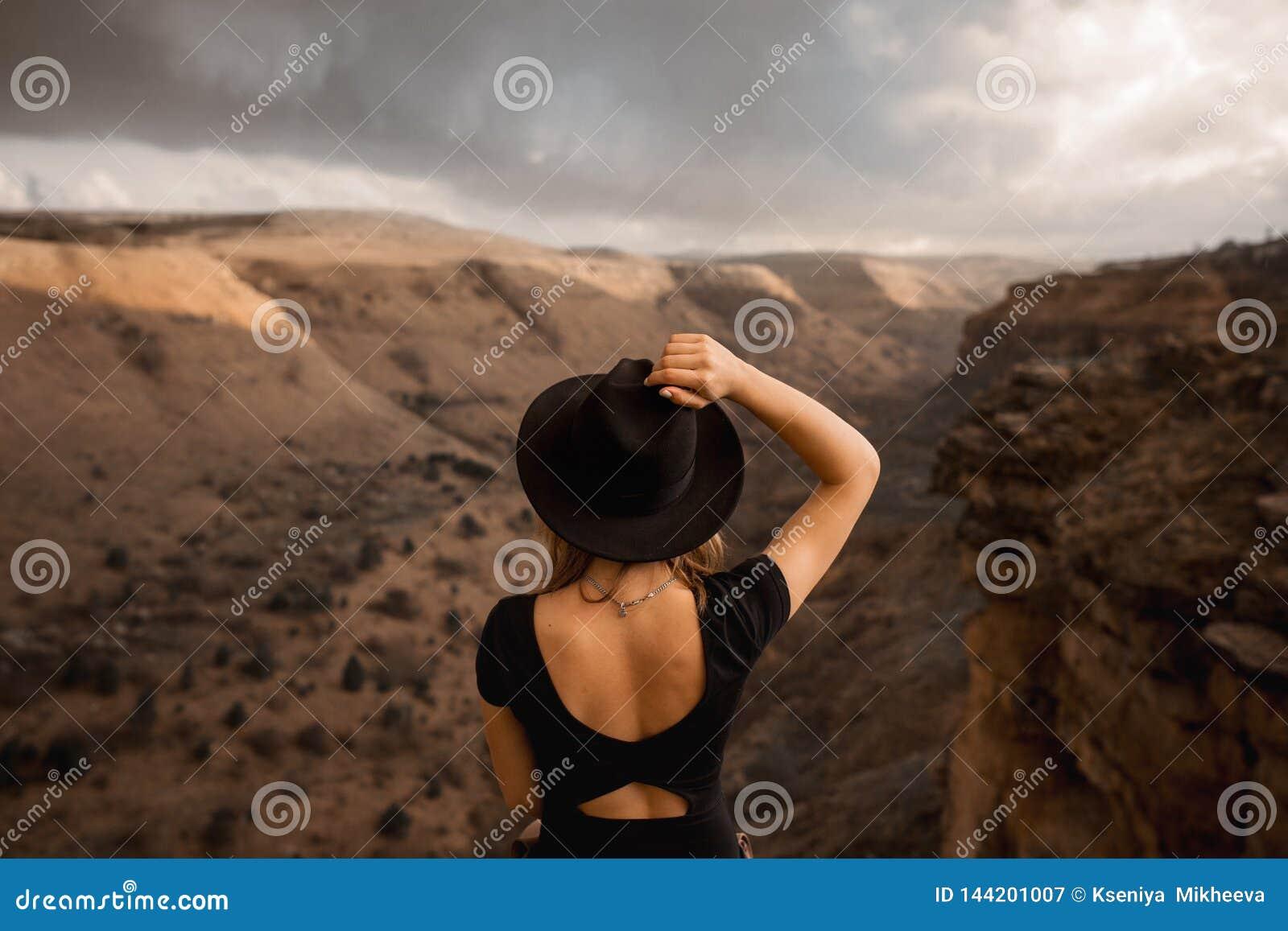Opinião traseira a jovem senhora do caminhante com a trouxa que senta-se no skywalk EUA do turismo da rocha excursão sightseeing