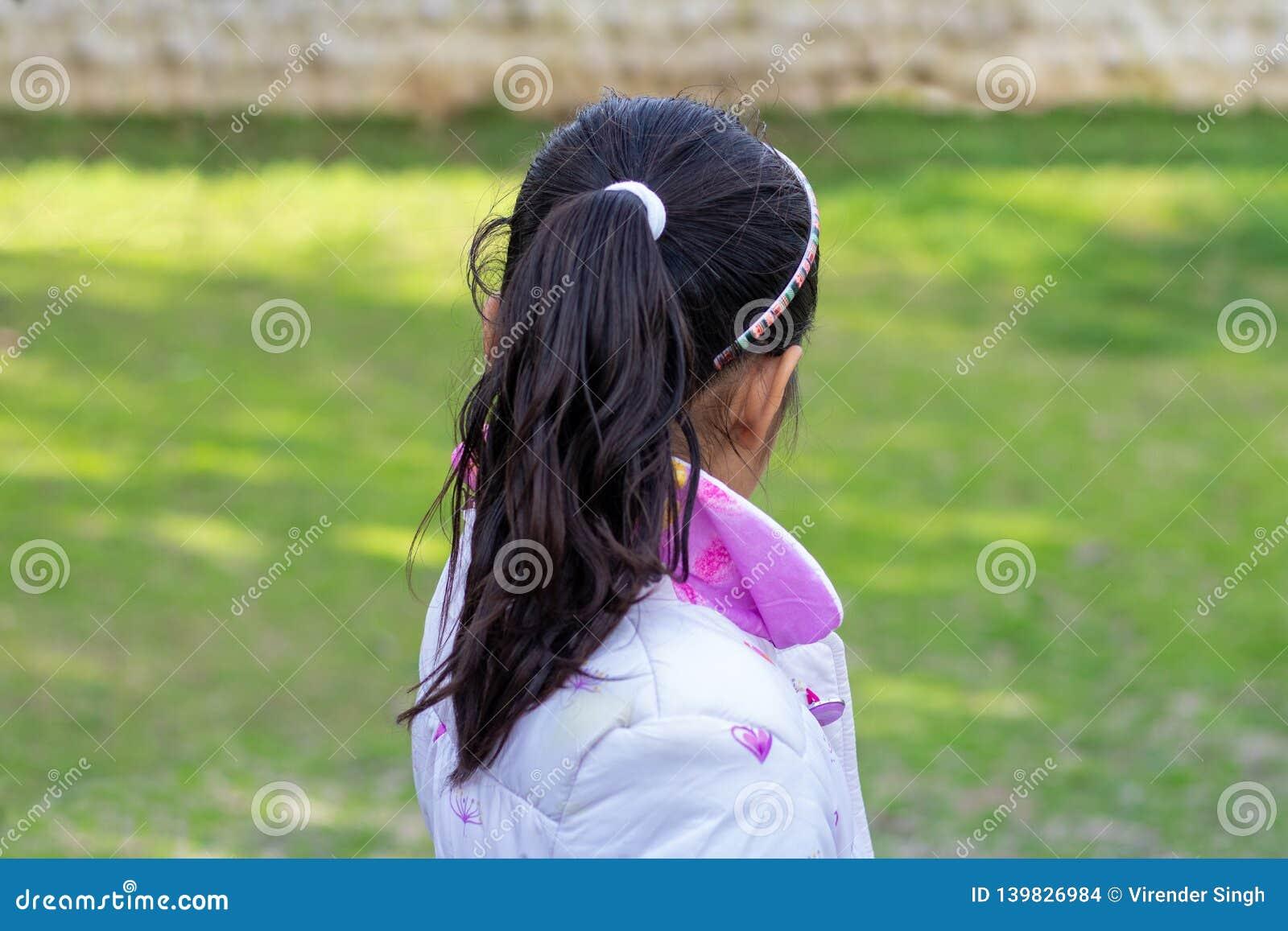 Opinião traseira a menina que olha algo