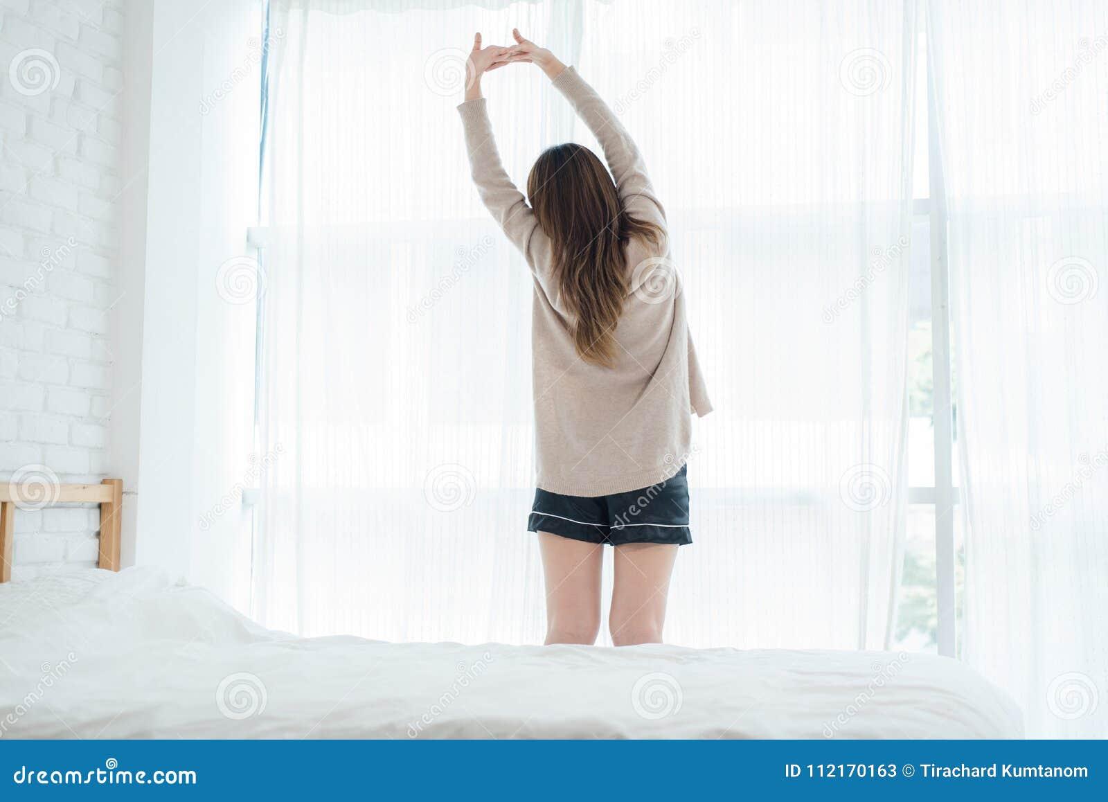 Opinião traseira a mulher asiática nova bonita feliz que acorda na manhã, sentando-se na cama, esticando no quarto acolhedor
