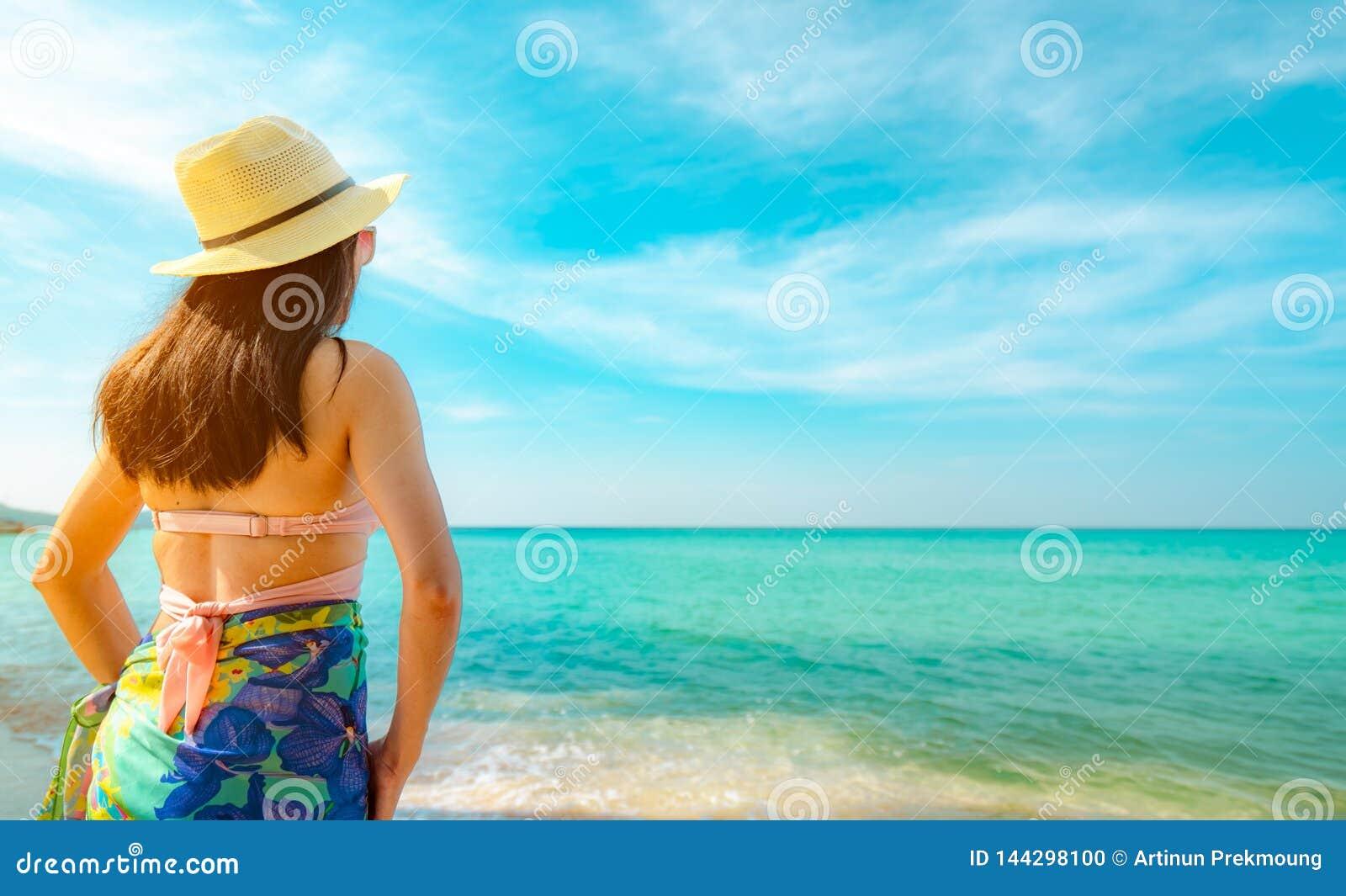 Opinião traseira a mulher asiática nova feliz com chapéu de palha para relaxar e apreciar o feriado na praia tropical do paraíso
