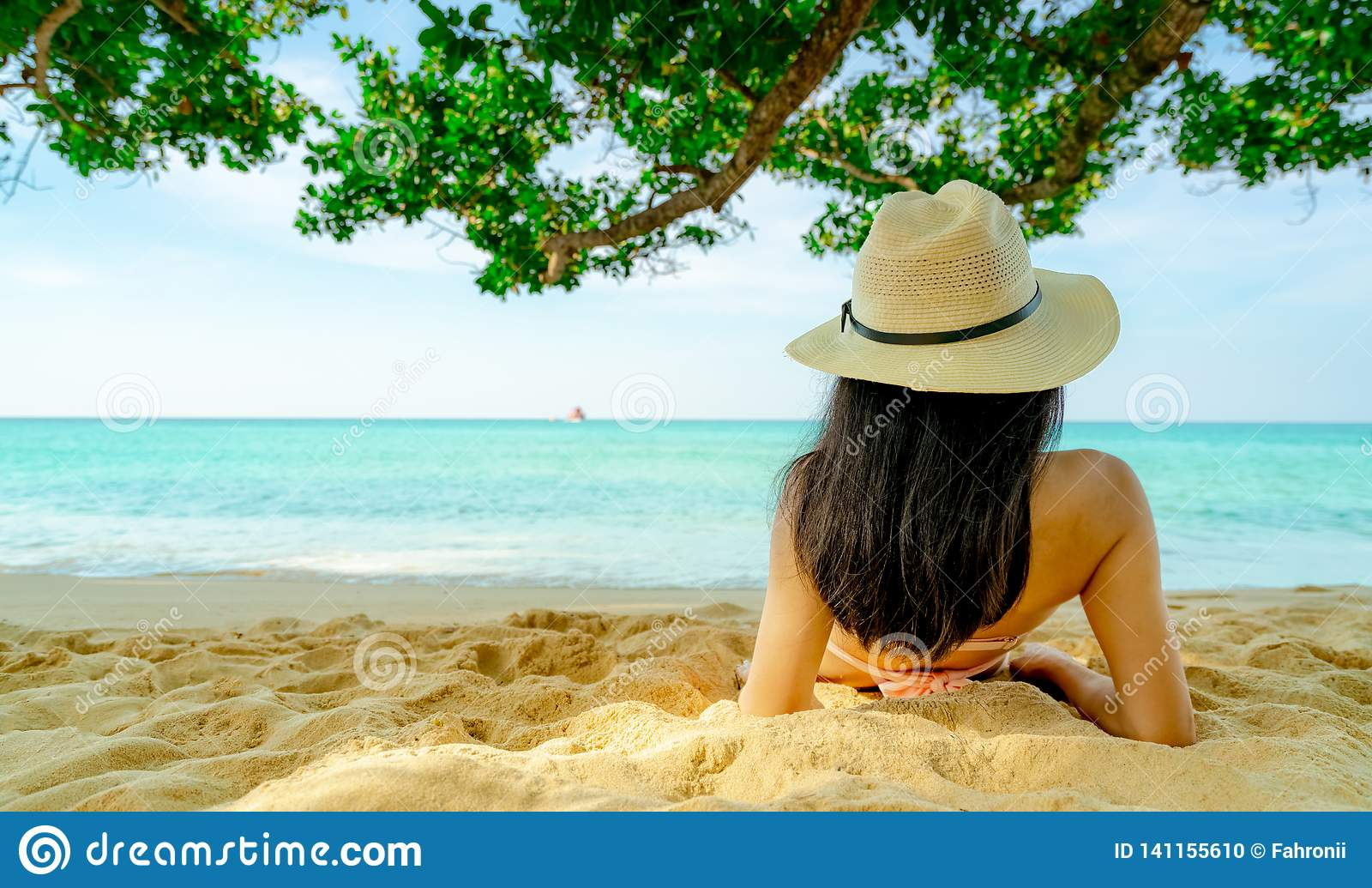 Opinião traseira a mulher asiática nova feliz no chapéu cor-de-rosa do roupa de banho e de palha para relaxar e apreciar o feriad