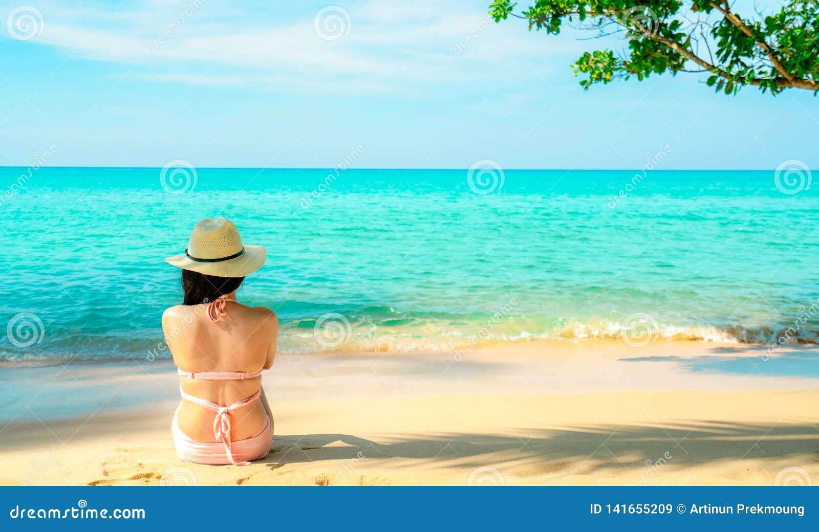 Opinião traseira a mulher asiática nova feliz no chapéu cor-de-rosa do roupa de banho e de palha que relaxa e para apreciar o fer