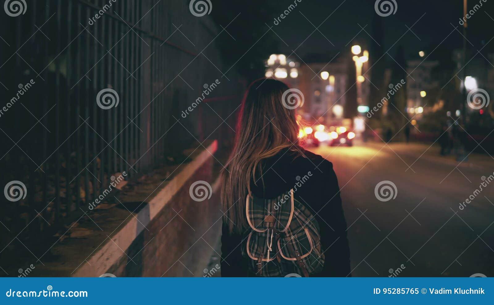 Opinião traseira a mulher moreno que anda perto da estrada no tempo do tráfego A menina atravessa a cidade tarde na noite apenas