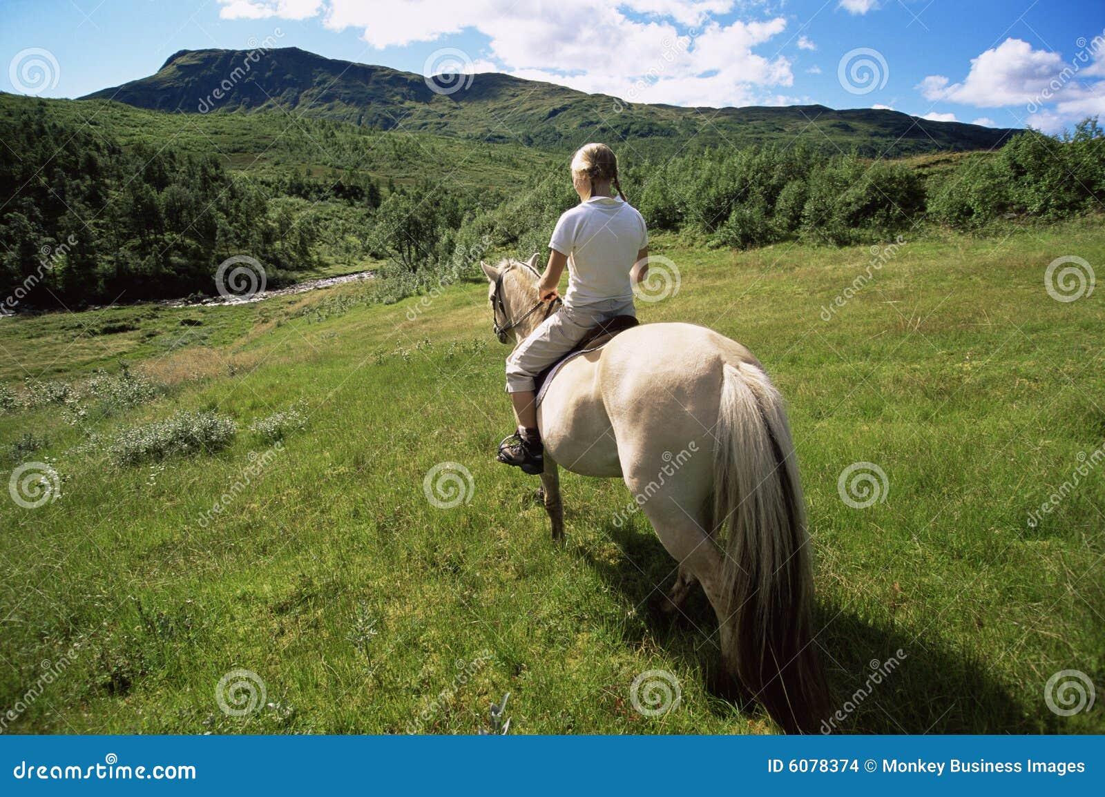 Opinião traseira o cavalo de equitação da mulher nova