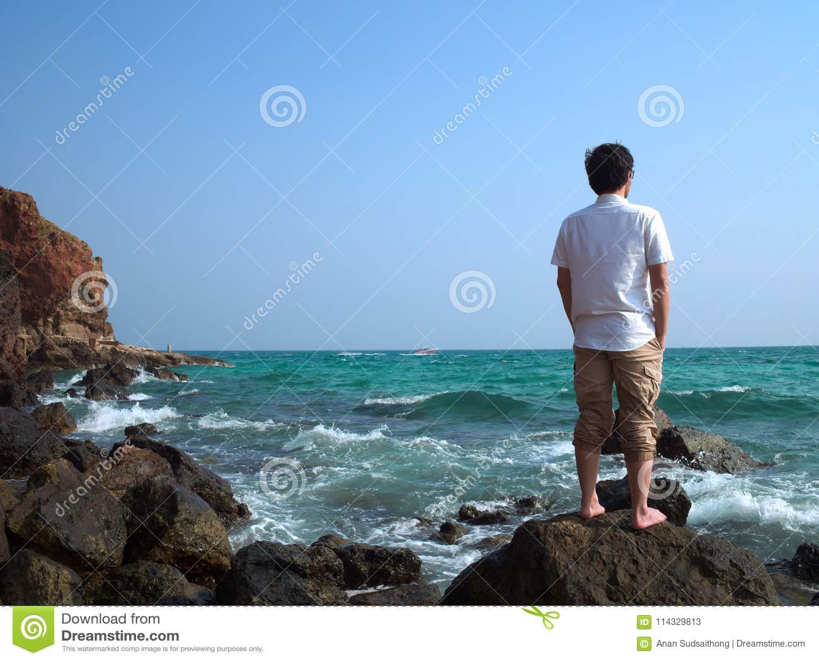 Opinião traseira o homem asiático só que está na pedra da costa de mar e que olha longe