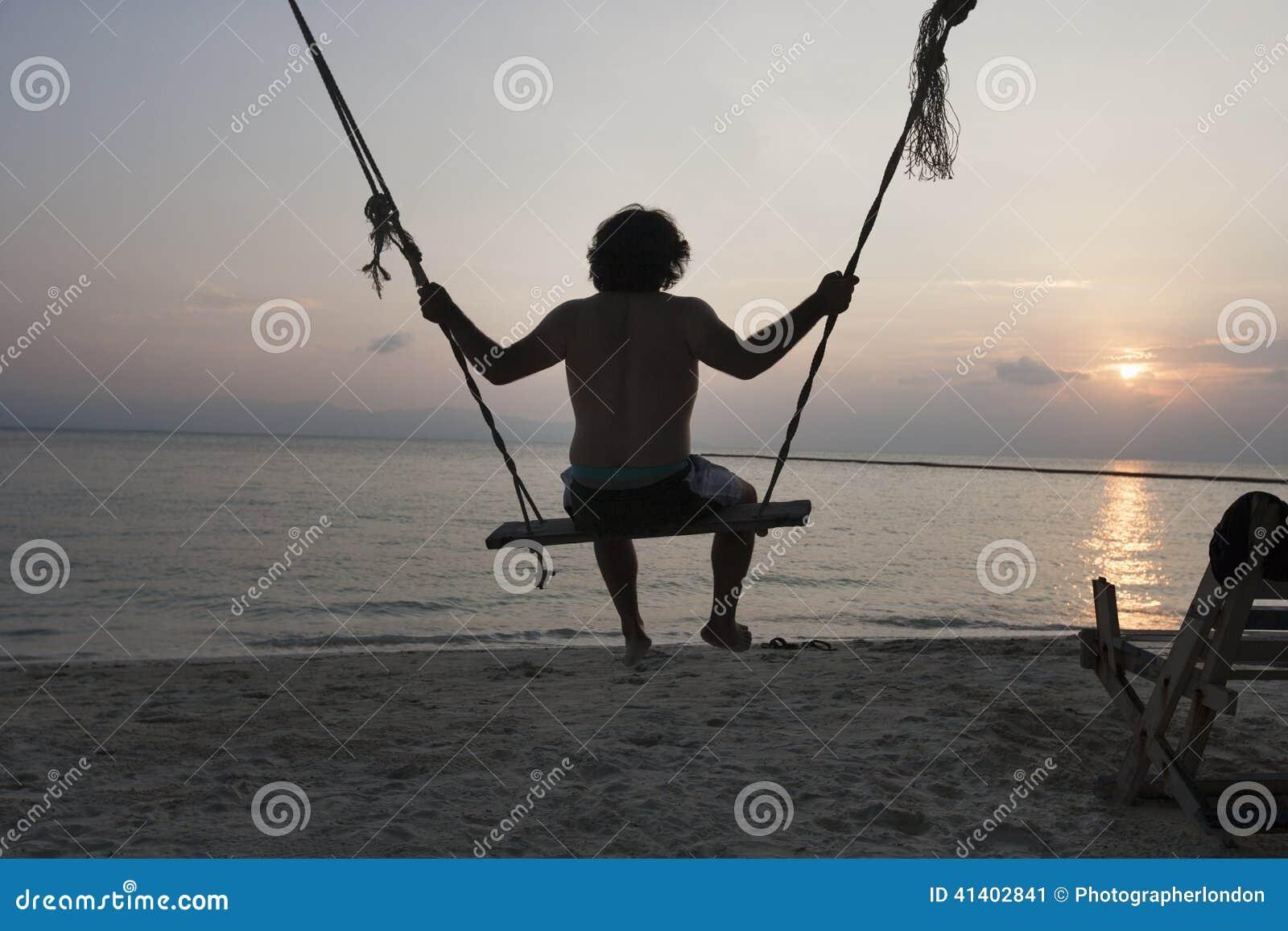 Opinião traseira o homem novo que balança na praia no por do sol