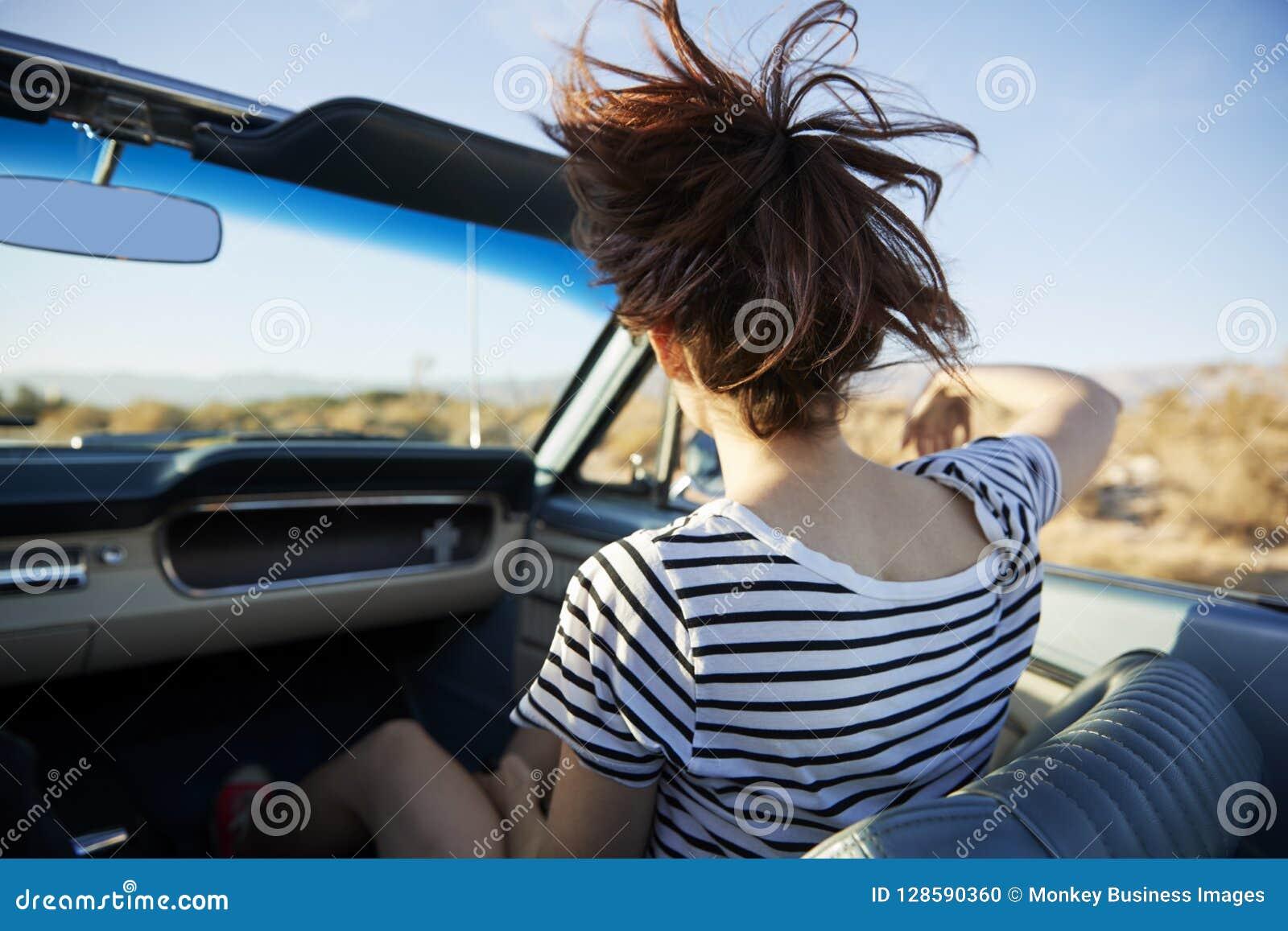 Opinião traseira o passageiro fêmea na viagem por estrada no carro convertível clássico