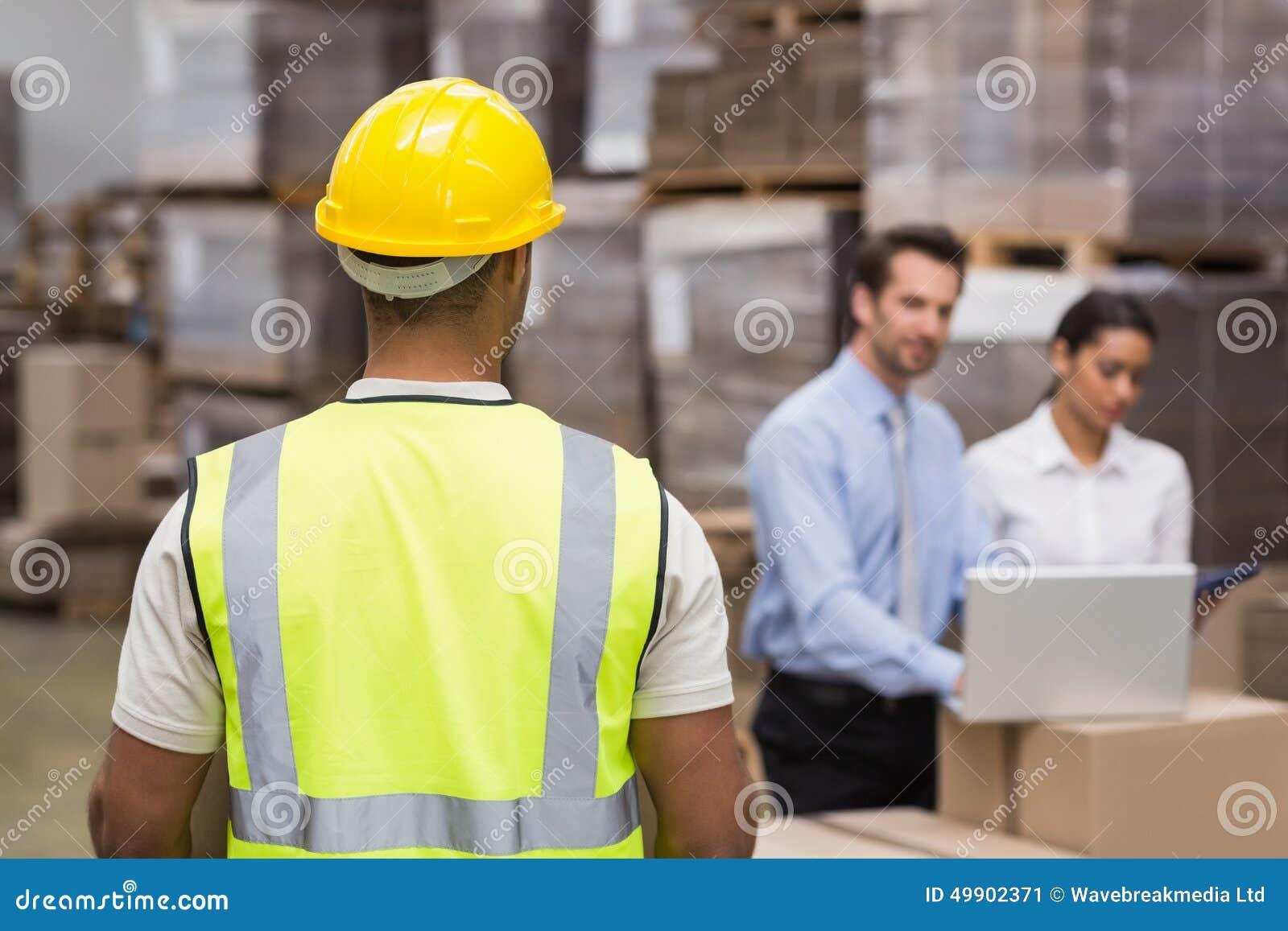 Opinião traseira o trabalhador do armazém na frente de seus gerentes