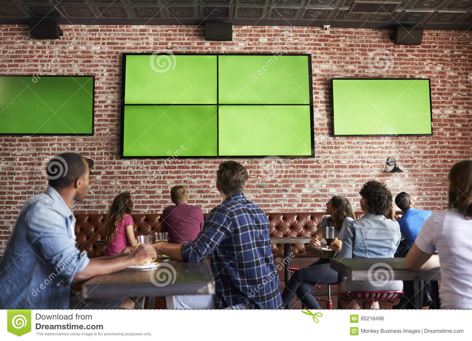 Opinião traseira os amigos que olham o jogo na barra de esportes em telas