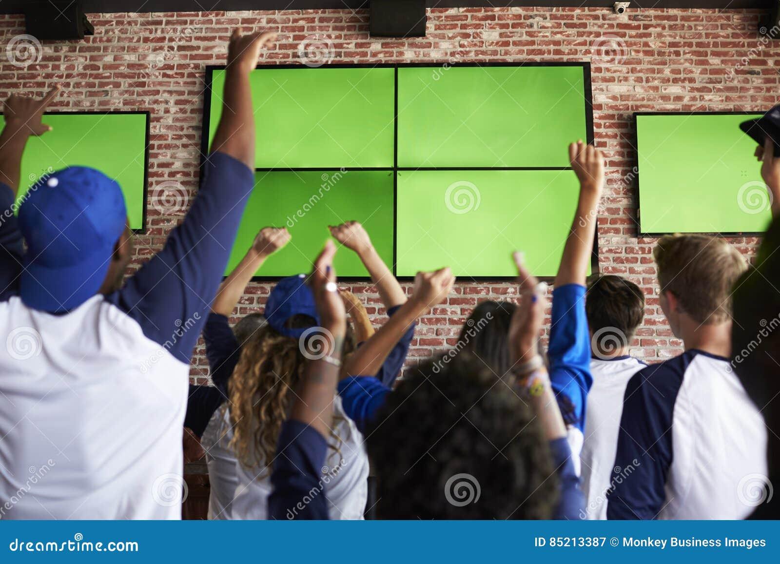 Opinião traseira os amigos que olham o jogo na comemoração da barra de esportes