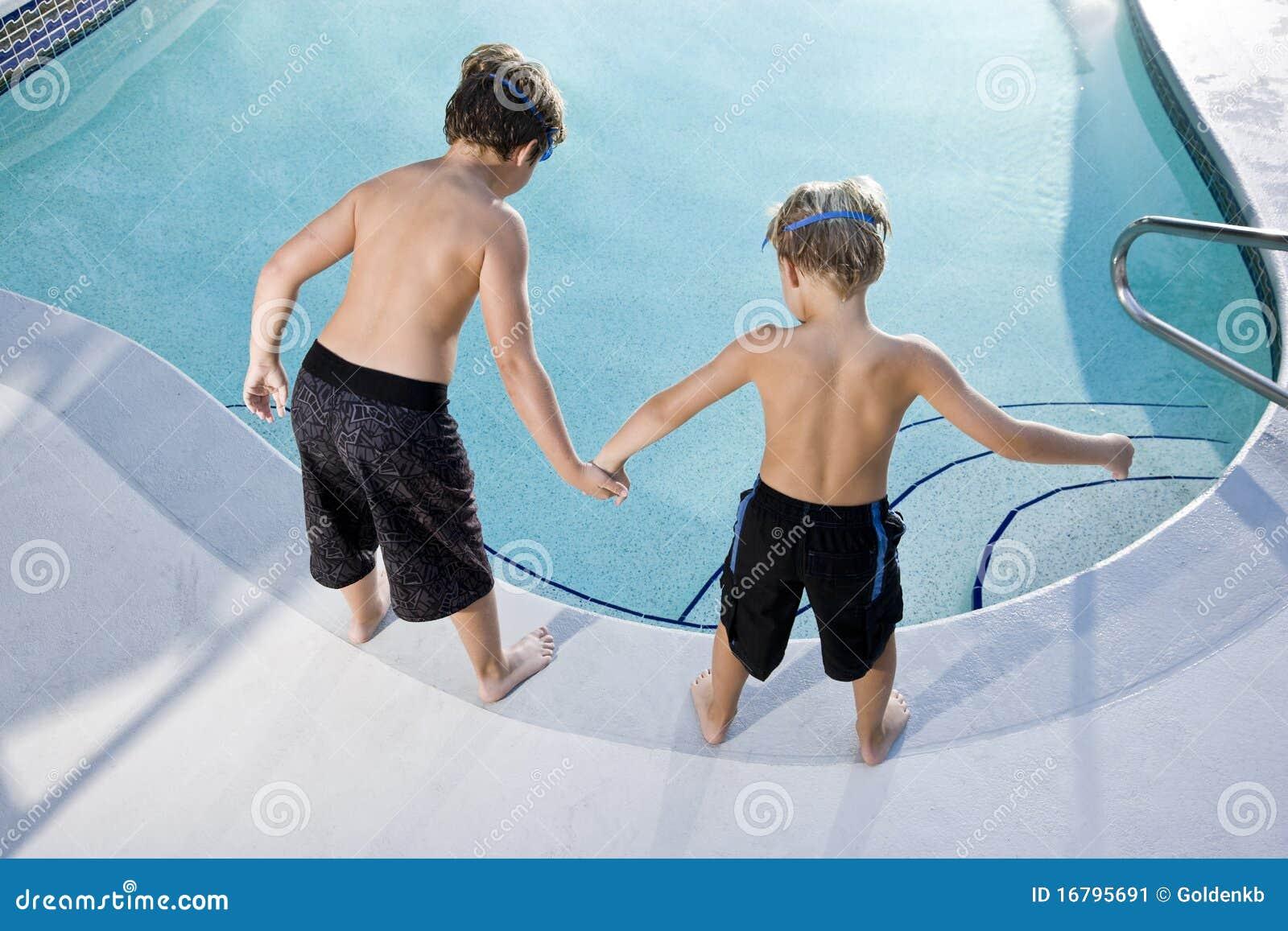 Opinião traseira os meninos que olham na piscina