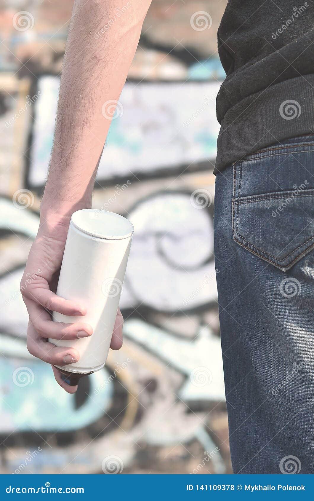 Opinião traseira um indivíduo que tira uma parede com pintura do aerossol