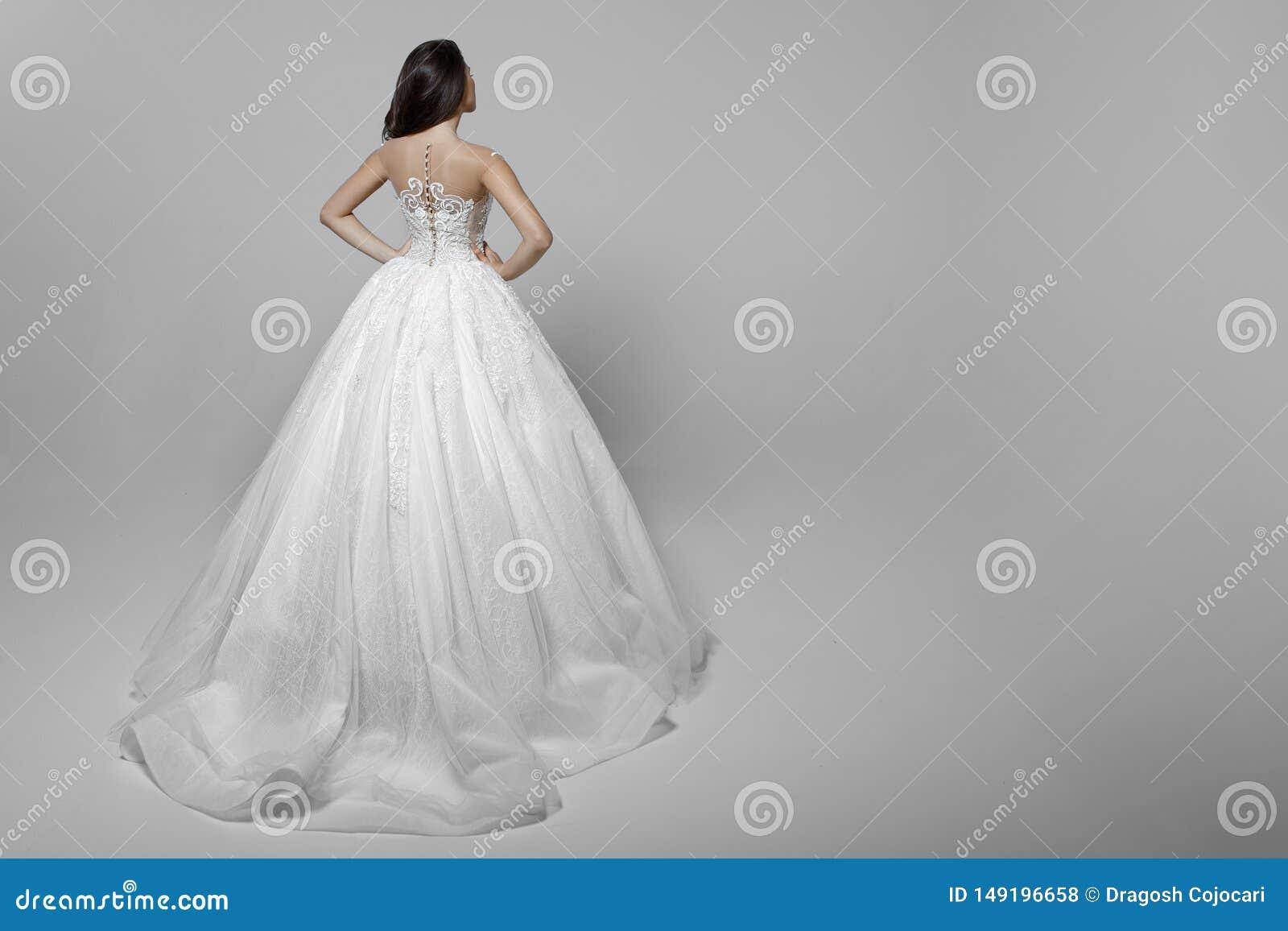 Opini?o traseira uma jovem mulher com cabelo longo no vestido de casamento branco, m?os em sua cintura, em um fundo branco