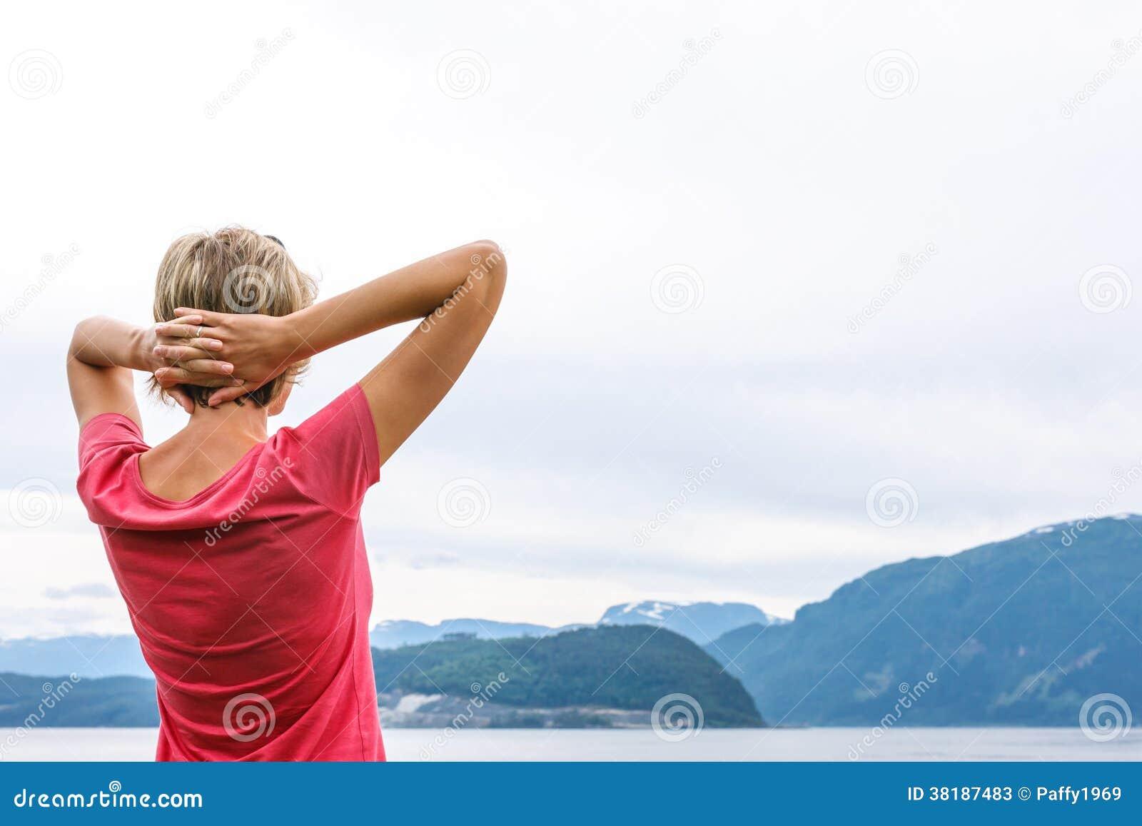 Opinião traseira uma mulher que aprecia uma vista no fiorde