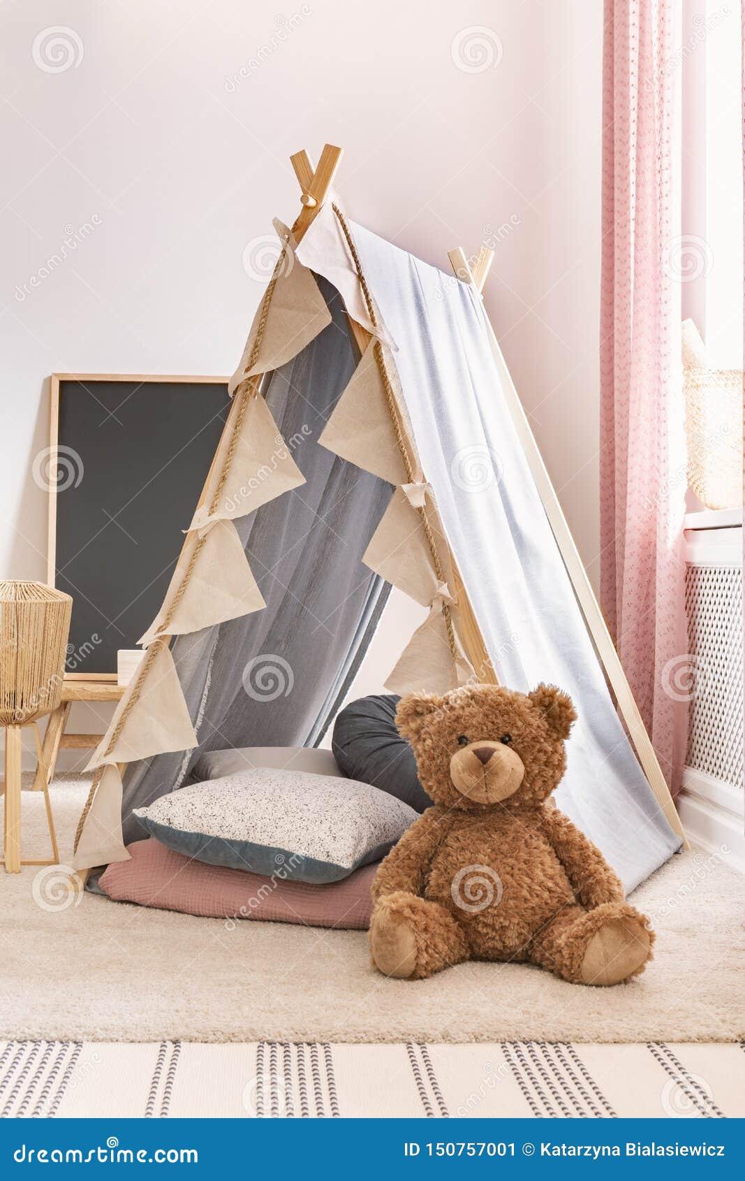Opinião vertical o urso de peluche ao lado da barraca com os descansos na sala de jogos bonito da criança, foto real