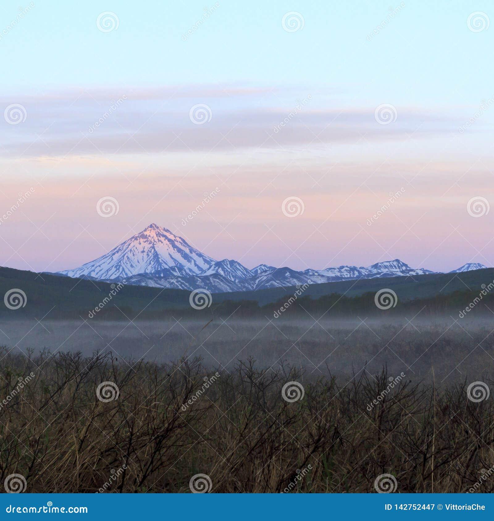 Opinião Volcano Vilyuchinsky no mornimg nevoento, península de Kamchatka, Rússia