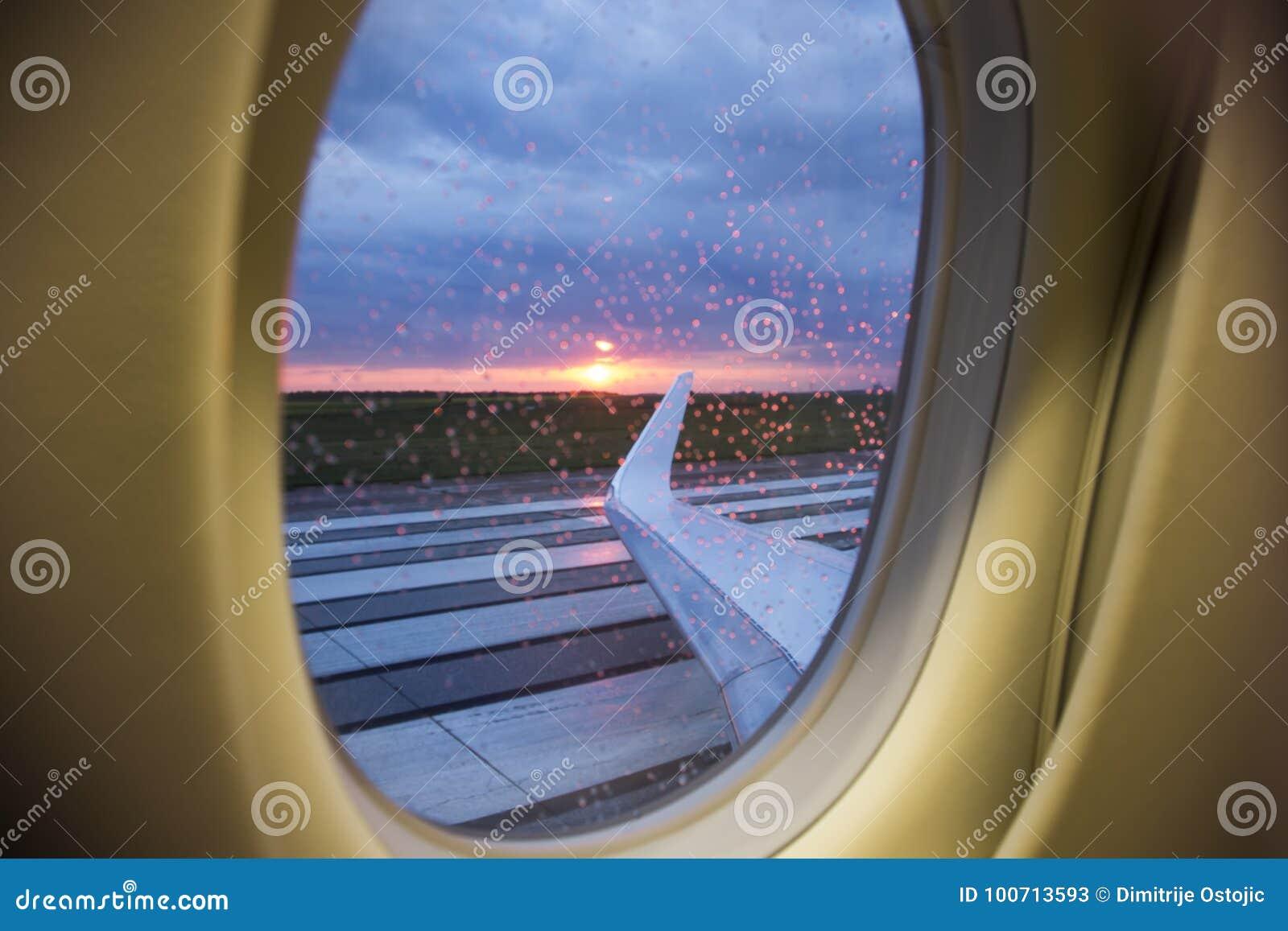 Opinión aérea de la salida del sol a través de la ventana del jet del negocio sobre las alas