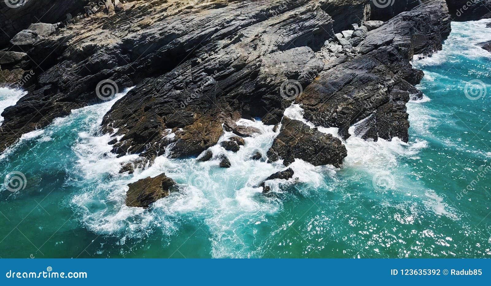 Opinión aérea del abejón del océano dramático que machaca en Rocky Landscape