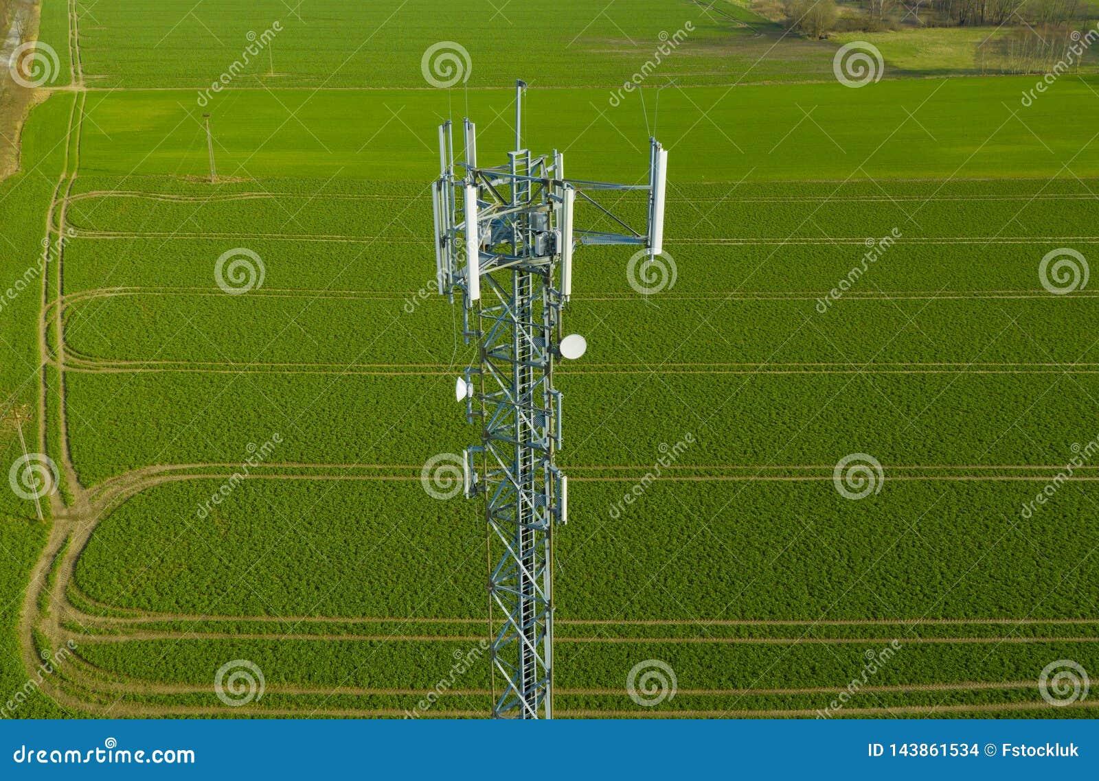 Opinión aérea sobre la torre de acero de la telecomunicación en el medio de la radio del campo verde, del teléfono y de la señal