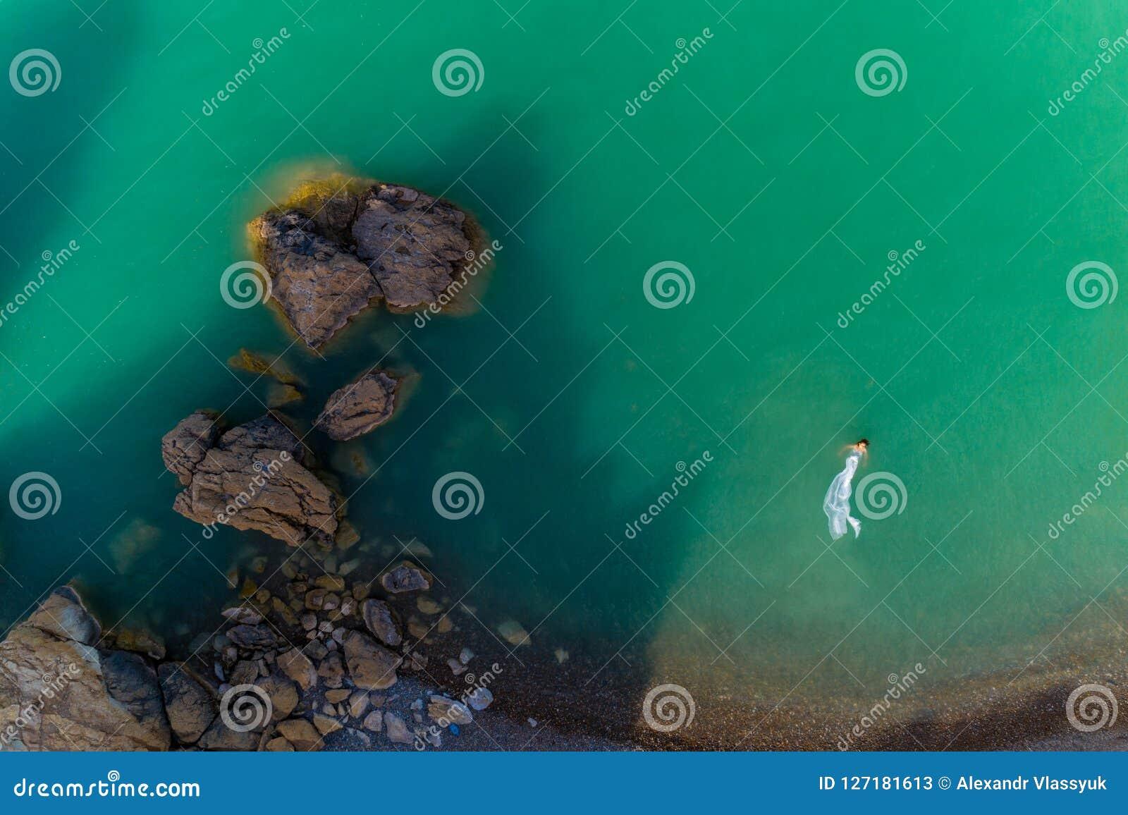 Opinión aérea una mujer joven que lleva un vestido blanco en las rocas Paisaje marino con una muchacha, playa, ondas hermosas, ro