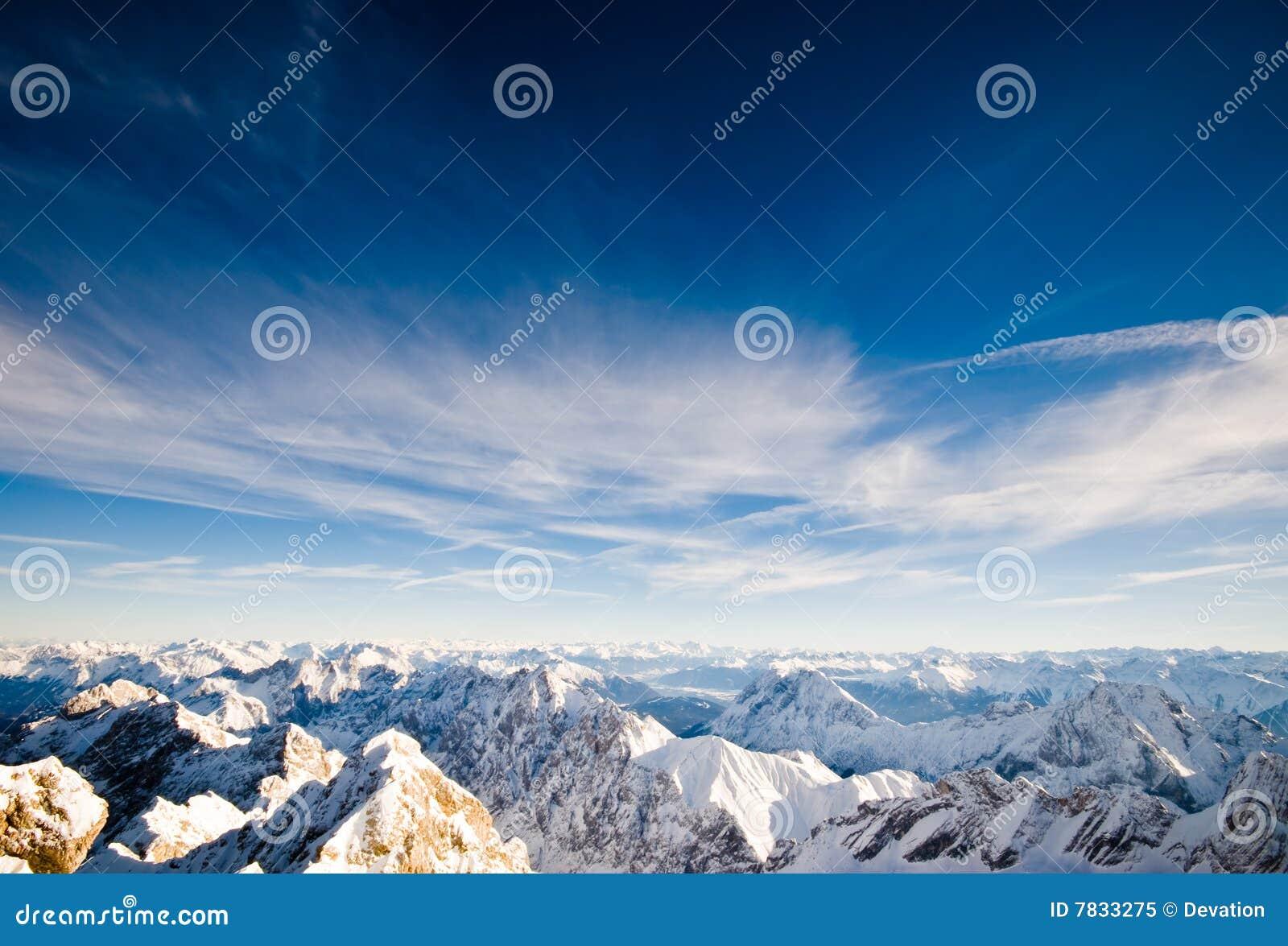 Opinión alpestre de la cima de la montaña del invierno