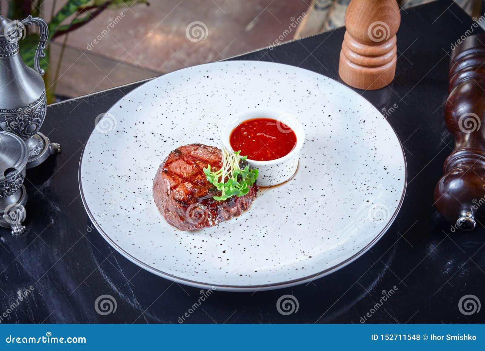Opinión ascendente cercana sobre la pequeña porción de filete de carne de vaca cocinada en la parrilla servida con la salsa roja