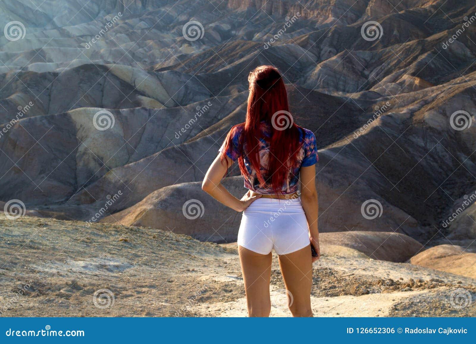 Opinión atractiva de la parte posterior de la mujer joven que se coloca delante del paisaje antiguo imponente del desierto, el lu
