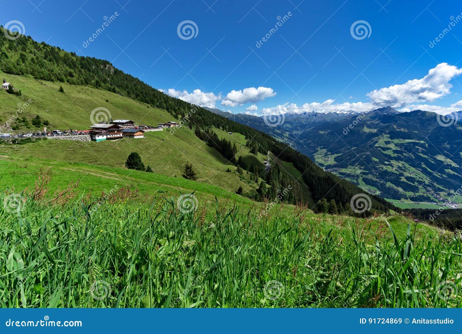 Opinión de ángulo bajo del prado verde y del pueblo alpino con las altas montañas debajo del cielo azul Austria, el Tirol, Ziller