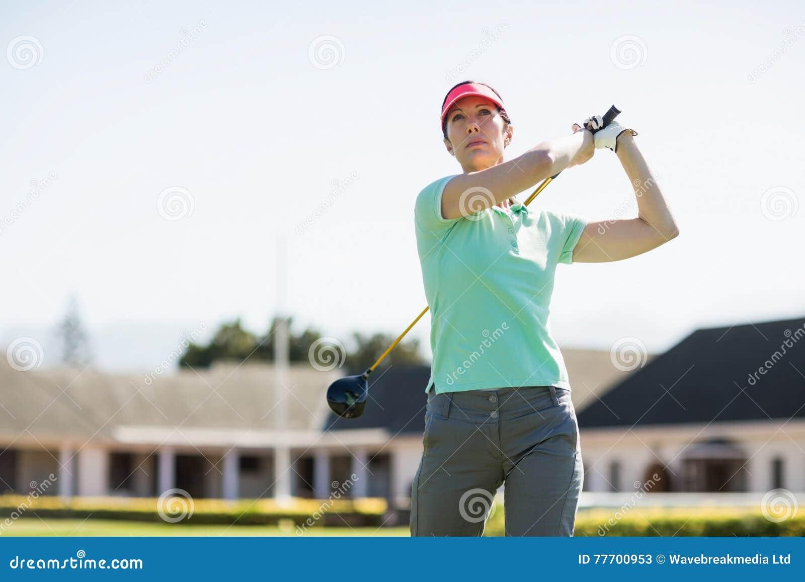 Opinión de ángulo bajo la mujer del golfista que toma el tiro